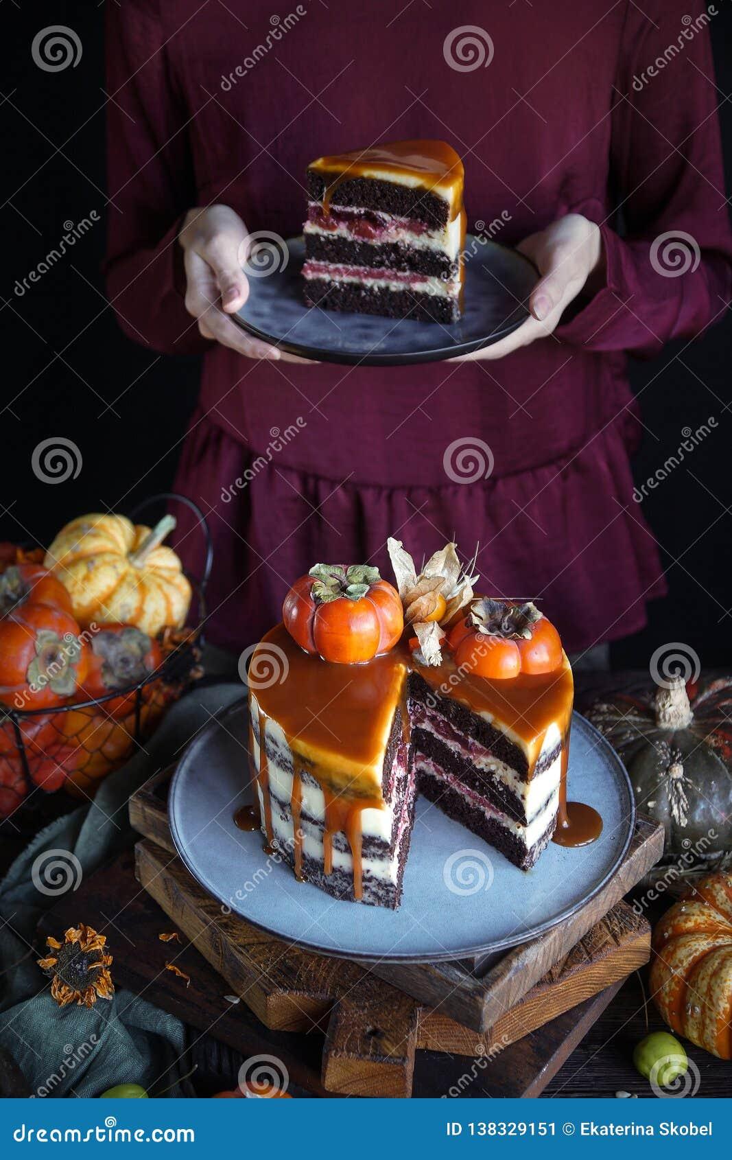 Bolo do outono com caqui e caramelo com uma abóbora e uma menina em um vestido de Borgonha em um fundo preto, alimento escuro atm