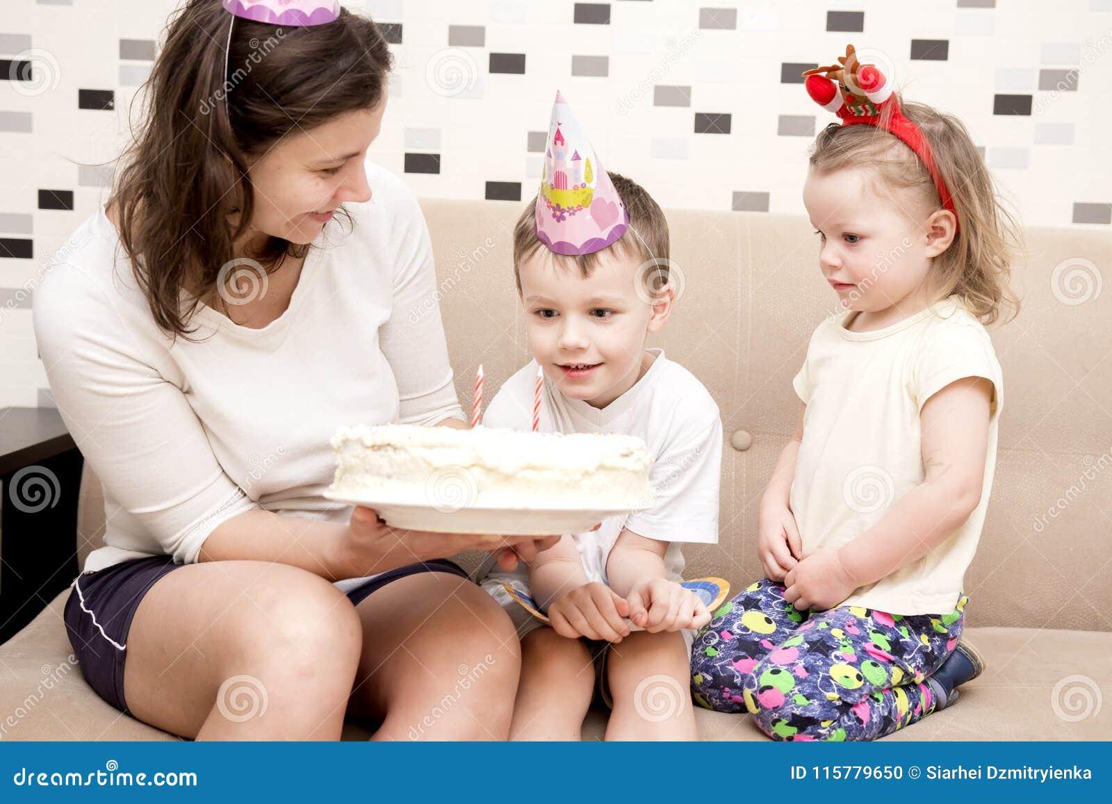 Bolo para o aniversário da criança A mamã guarda o bolo de aniversário para o aniversário do ` s das crianças