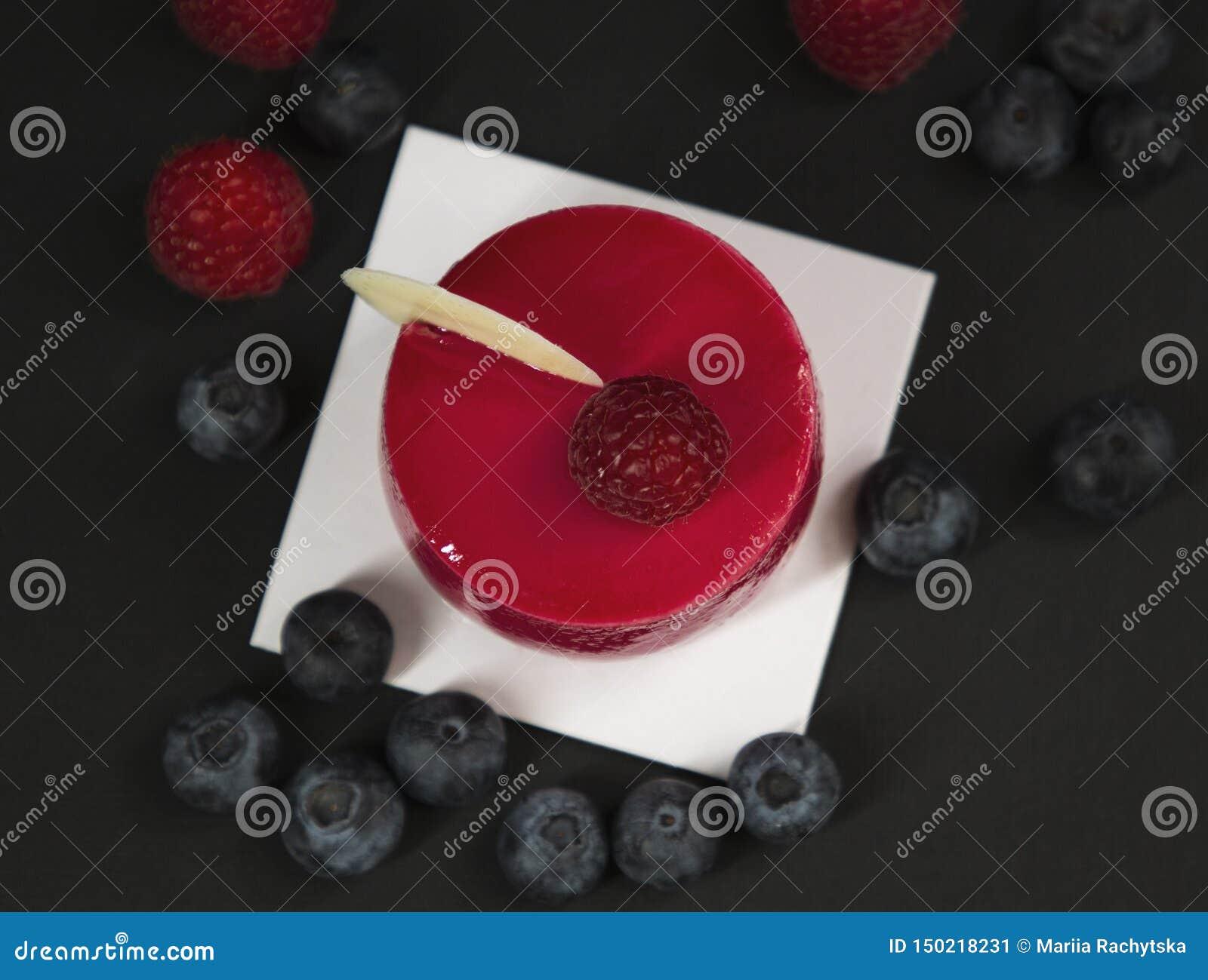 Bolo vermelho à moda bonito novo no esmalte com framboesas