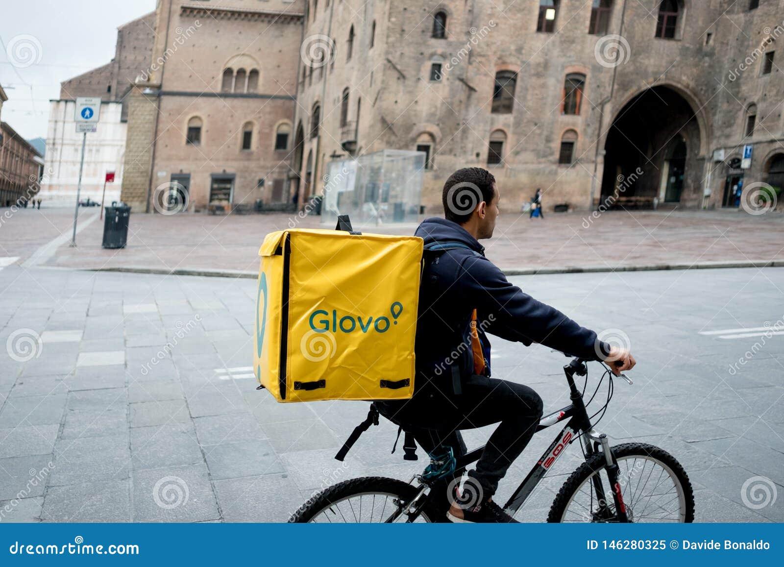 Bologna, Italia - 13 aprile 2019: giovane cavaliere di glovo che effettua consegna sul suo funzionamento della bici nella cosidde