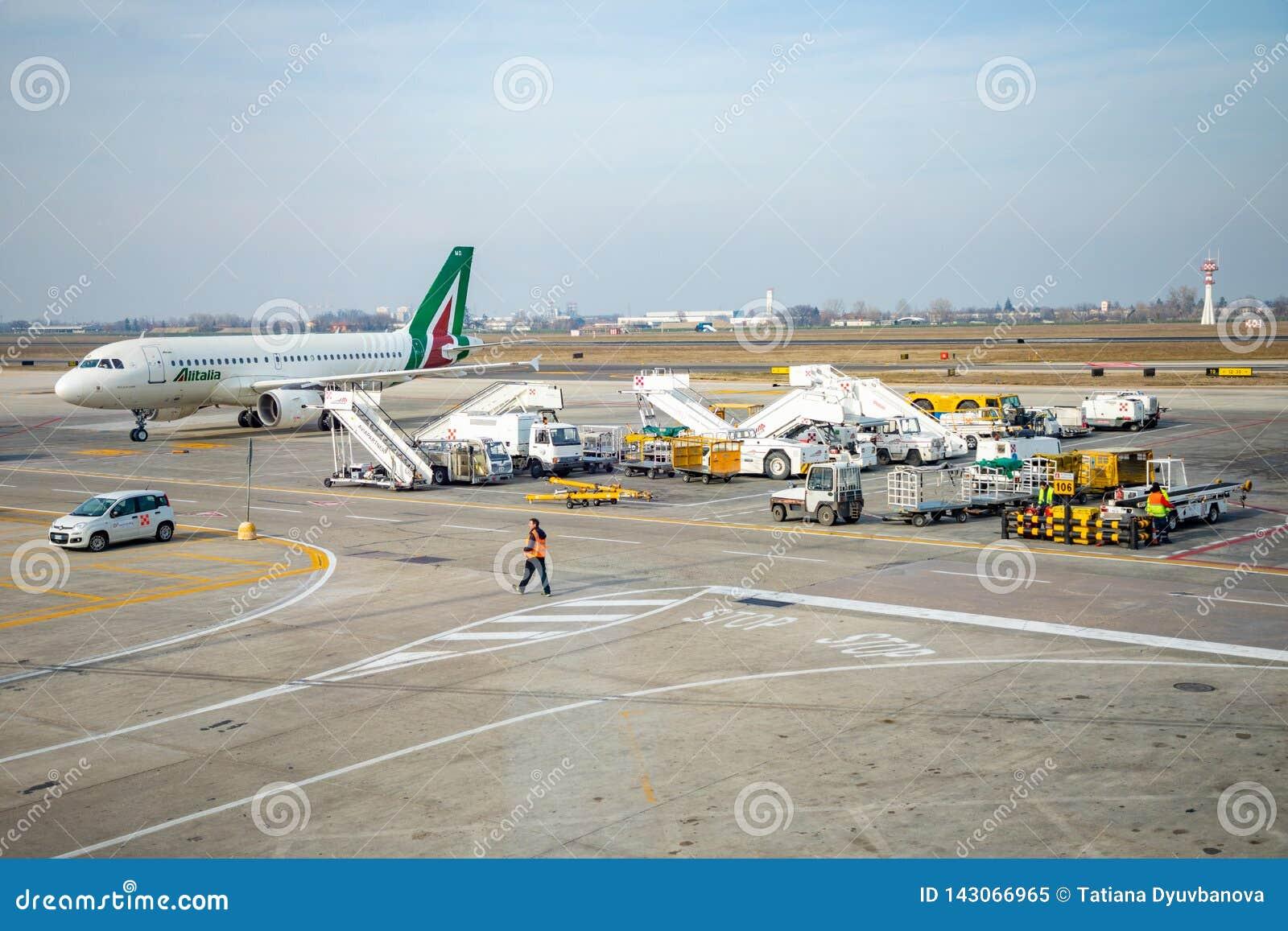 Bologna Italien - 10 02 2019: Upptagen flygplatssikt med flygplan- och servicemedel-, lopp- och branschbegrepp