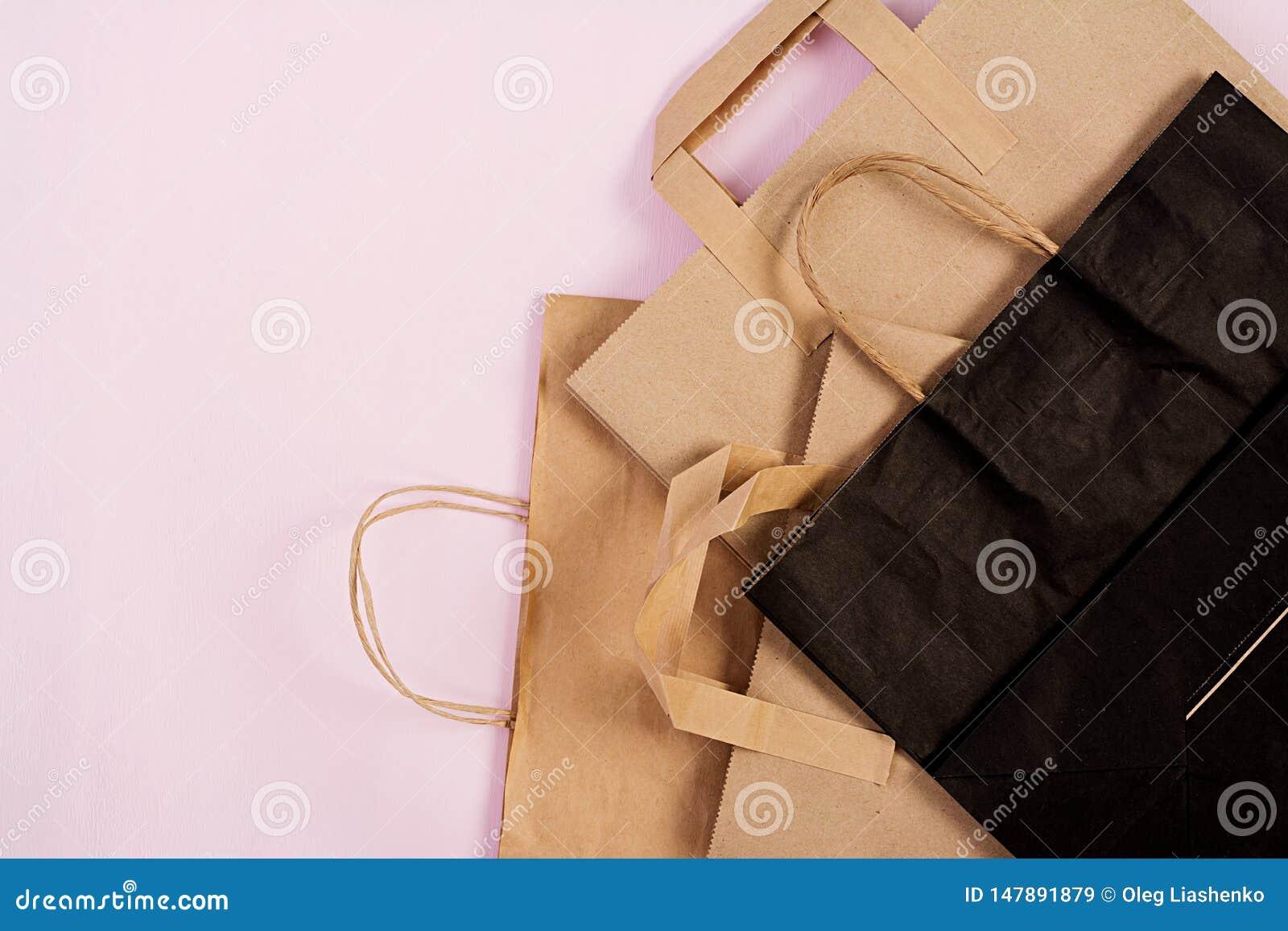 Bolsa de papel reciclable de Differents en fondo rosado Eco que recicla concepto Visi?n superior