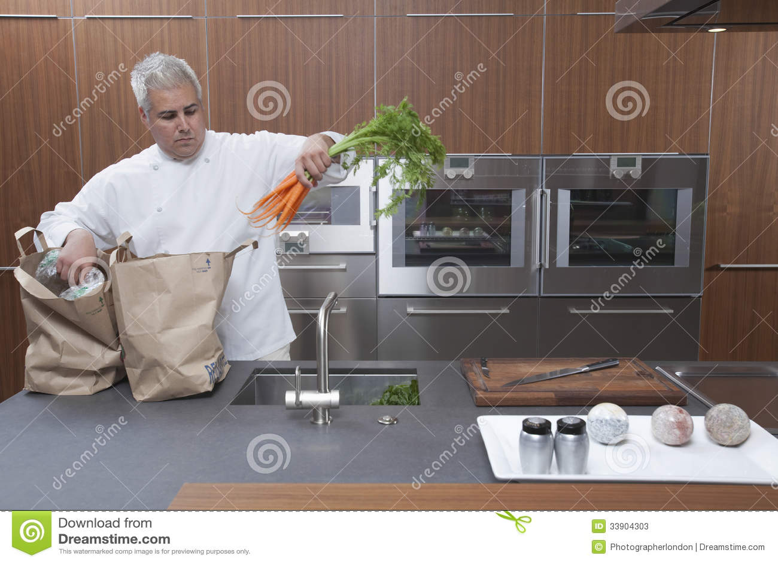 Bolsas de papel de Unpacking Carrots From del cocinero en cocina