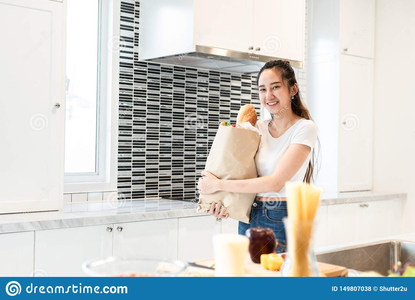 Bolso asi?tico de la tenencia de la mujer de la belleza de los ingredientes para cocinar despu?s de compras en la gente del super