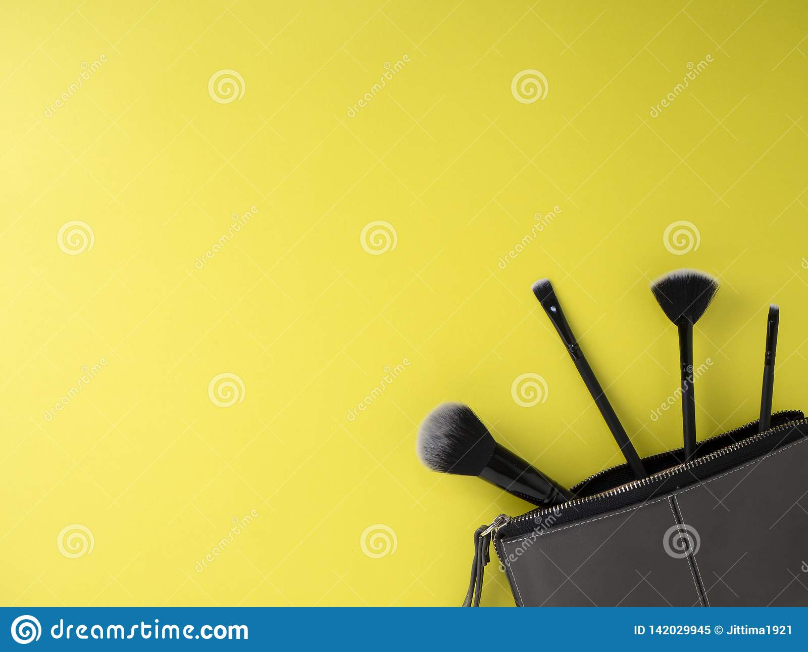 Bolso con los cepillos del maquillaje, cosméticos, fondo amarillo