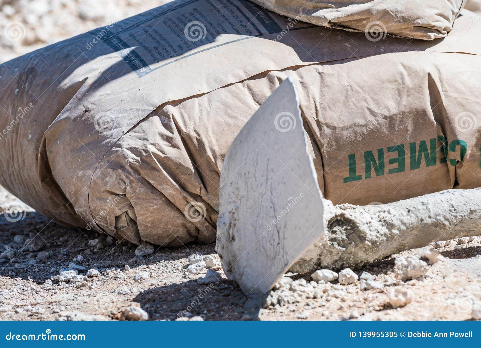 Bolso marrón cerrado del cemento y una azada en la tierra