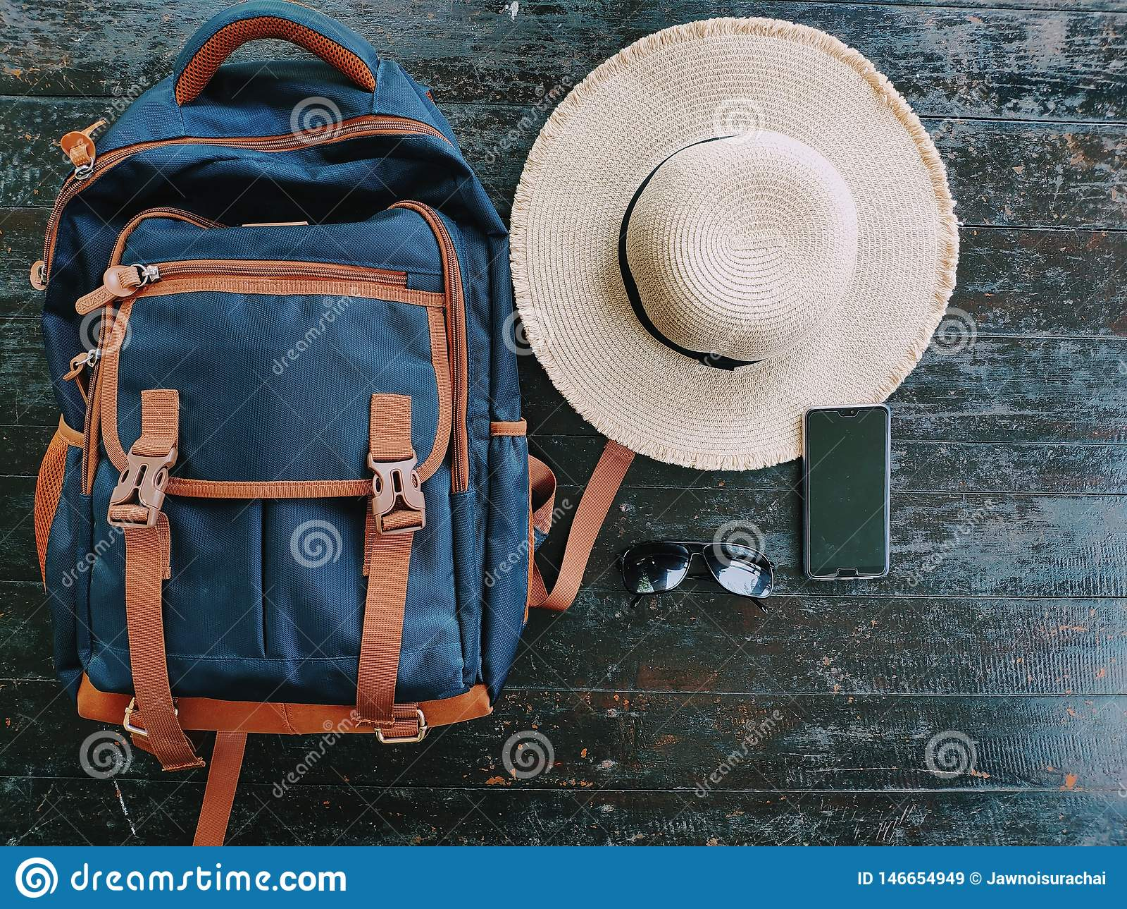 Bolso que viaja, sombrero, vidrios de sol, teléfono móvil, colocado en una tabla de madera preparada para viajar durante las vaca
