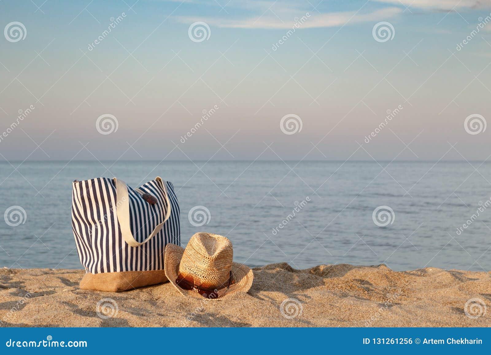 Bolso rayado del verano con el sombrero de paja y las gafas de sol en la playa, fondo del mar tranquilo Tiempo de la puesta del s