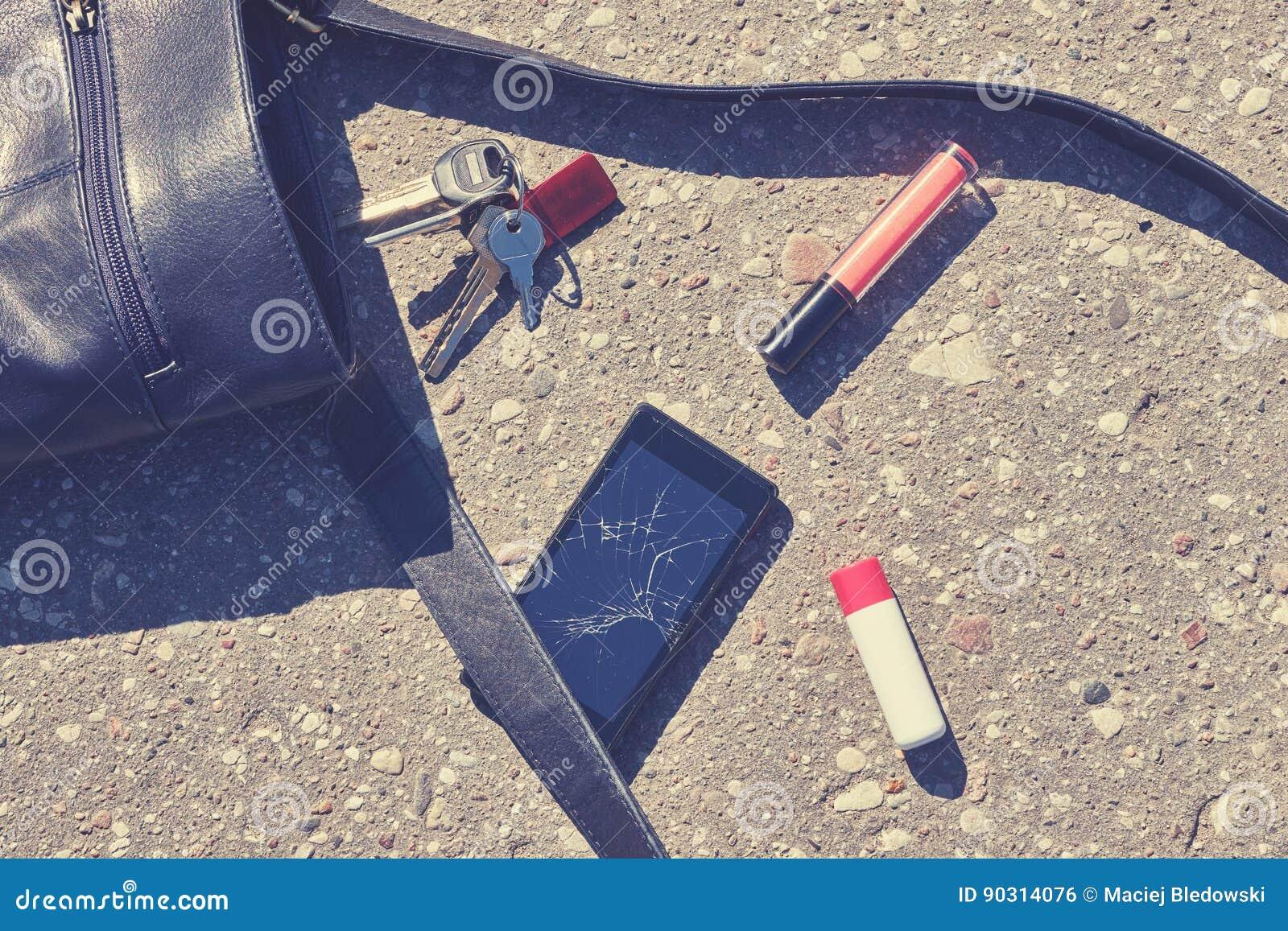 Bolso, teléfono roto, llaves y lápiz labial en la calle del asfalto