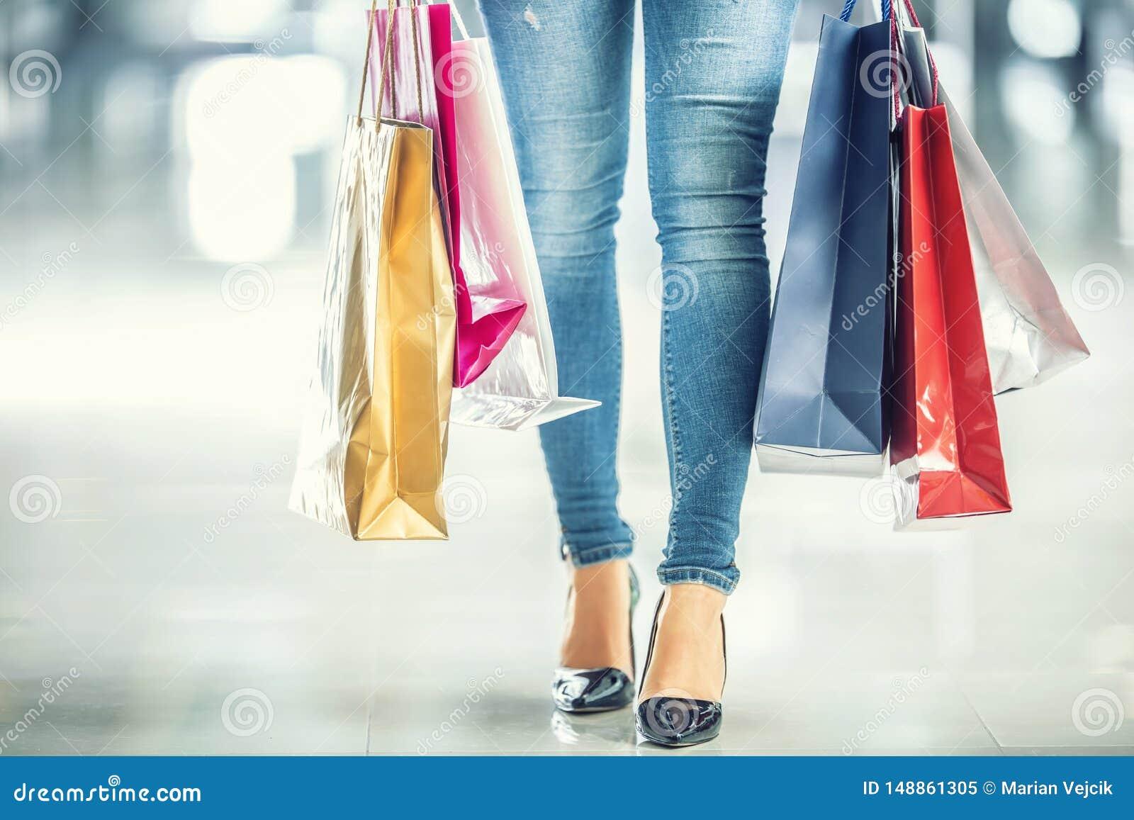 Bolsos que hacen compras coloridos en las manos de una mujer de los compradores y sus vaqueros y zapatos de las piernas