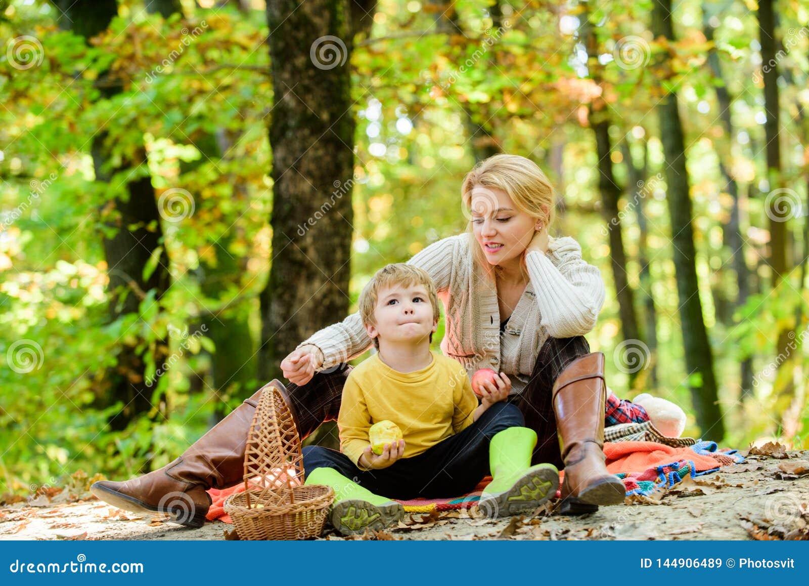 Bom dia para o piquenique da mola na natureza Comendo o petisco durante a caminhada Inf?ncia feliz Menino da mam? e da crian?a qu