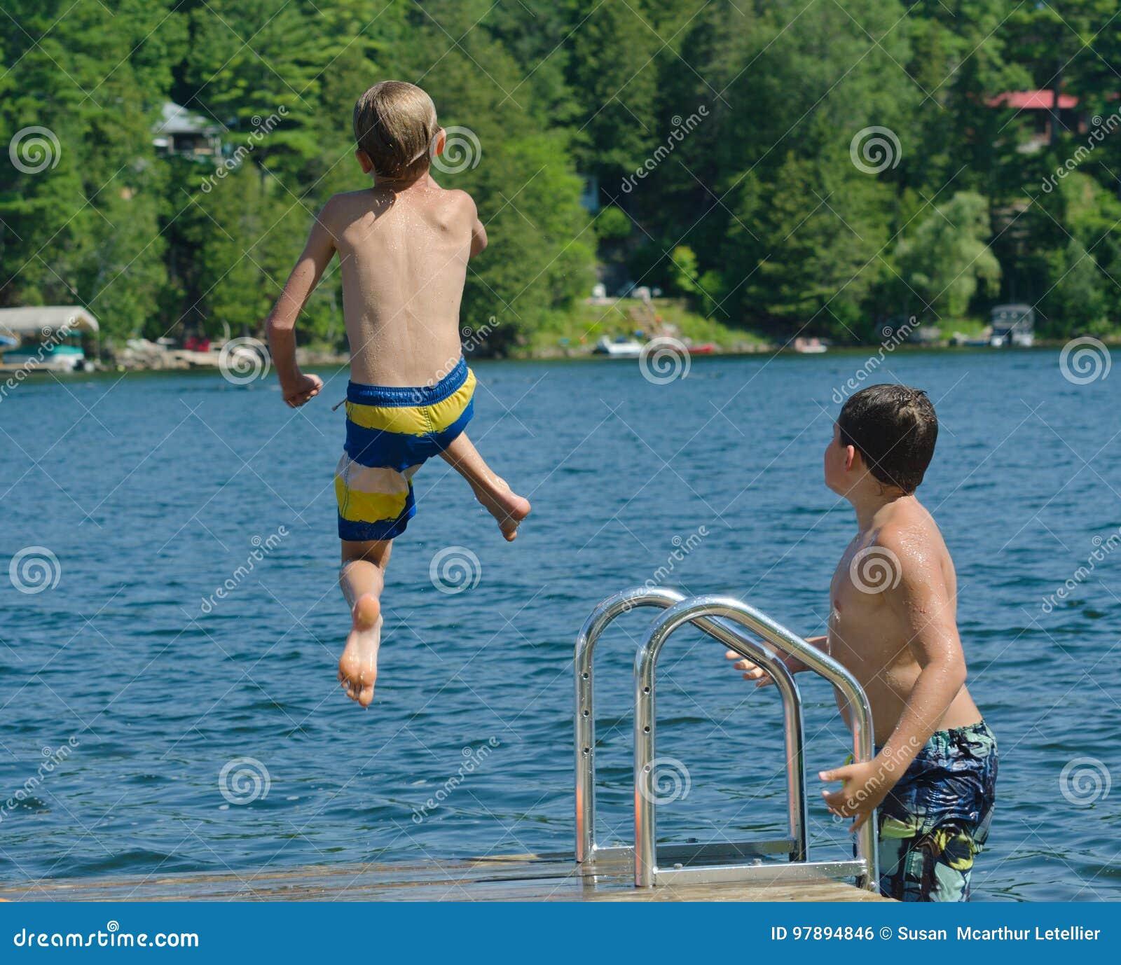 Bombardeio de mergulho do menino fora da doca no lago