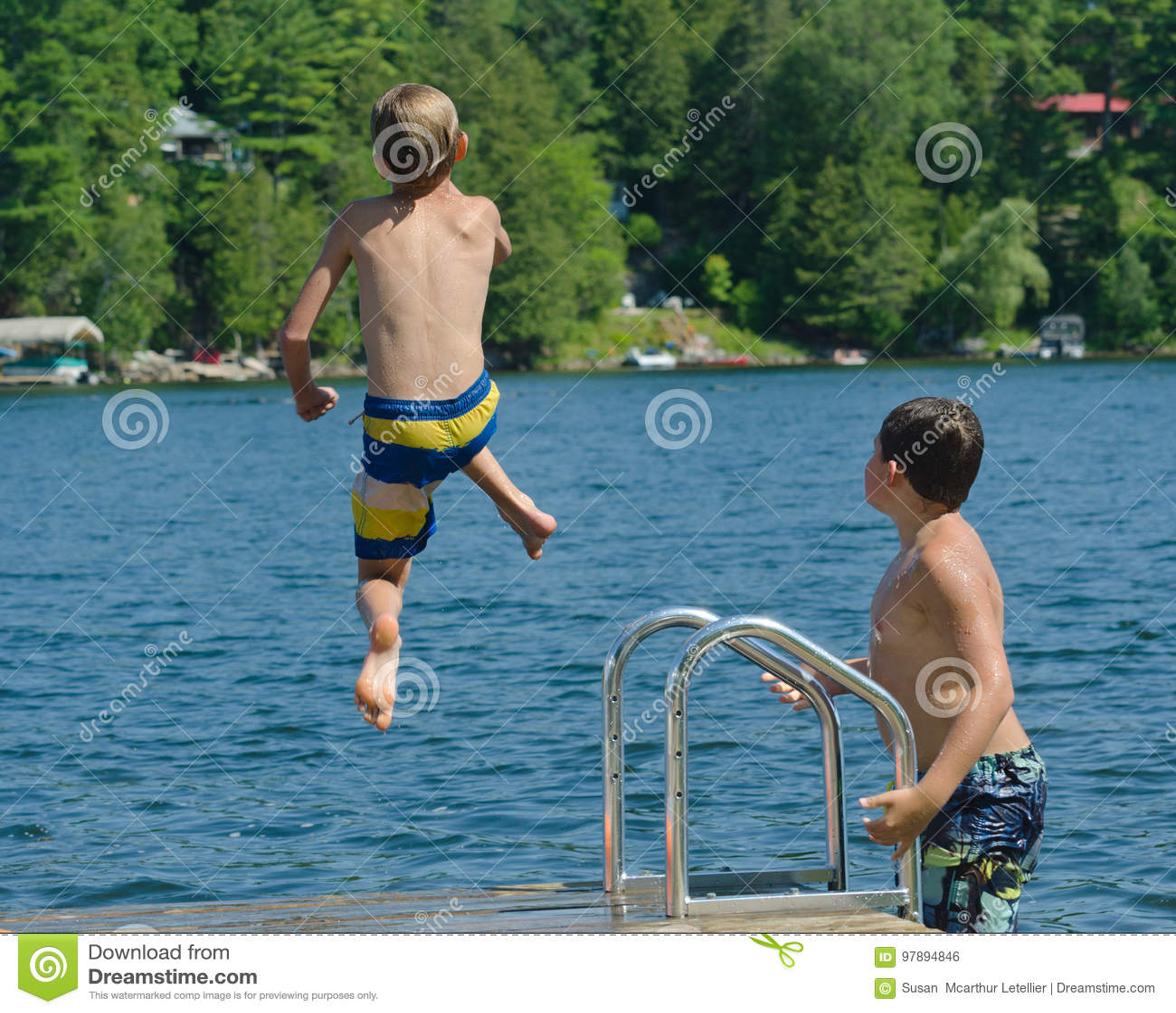 Bombardement de piqué de garçon outre de dock dans le lac