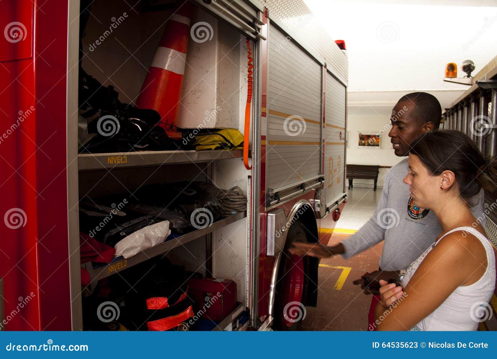 Bombeiro que explica as ferramentas diferentes em um carro de bombeiros