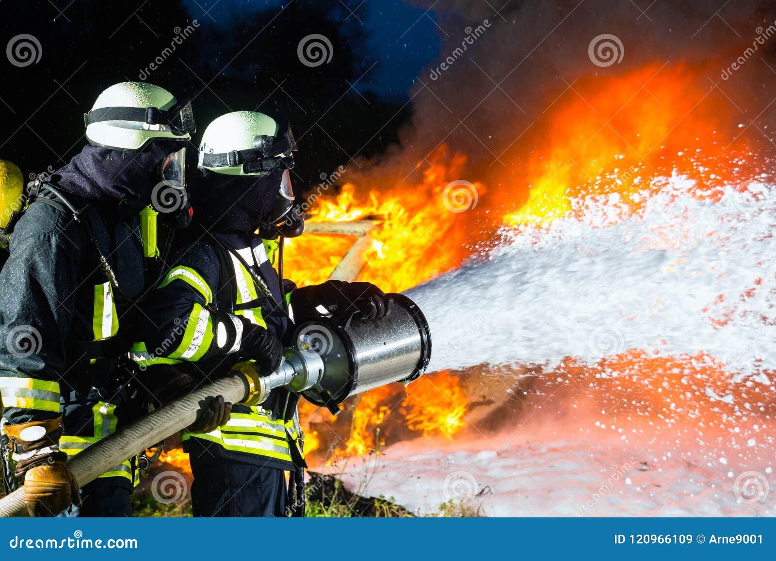 Bombero - bomberos que extinguen un resplandor grande