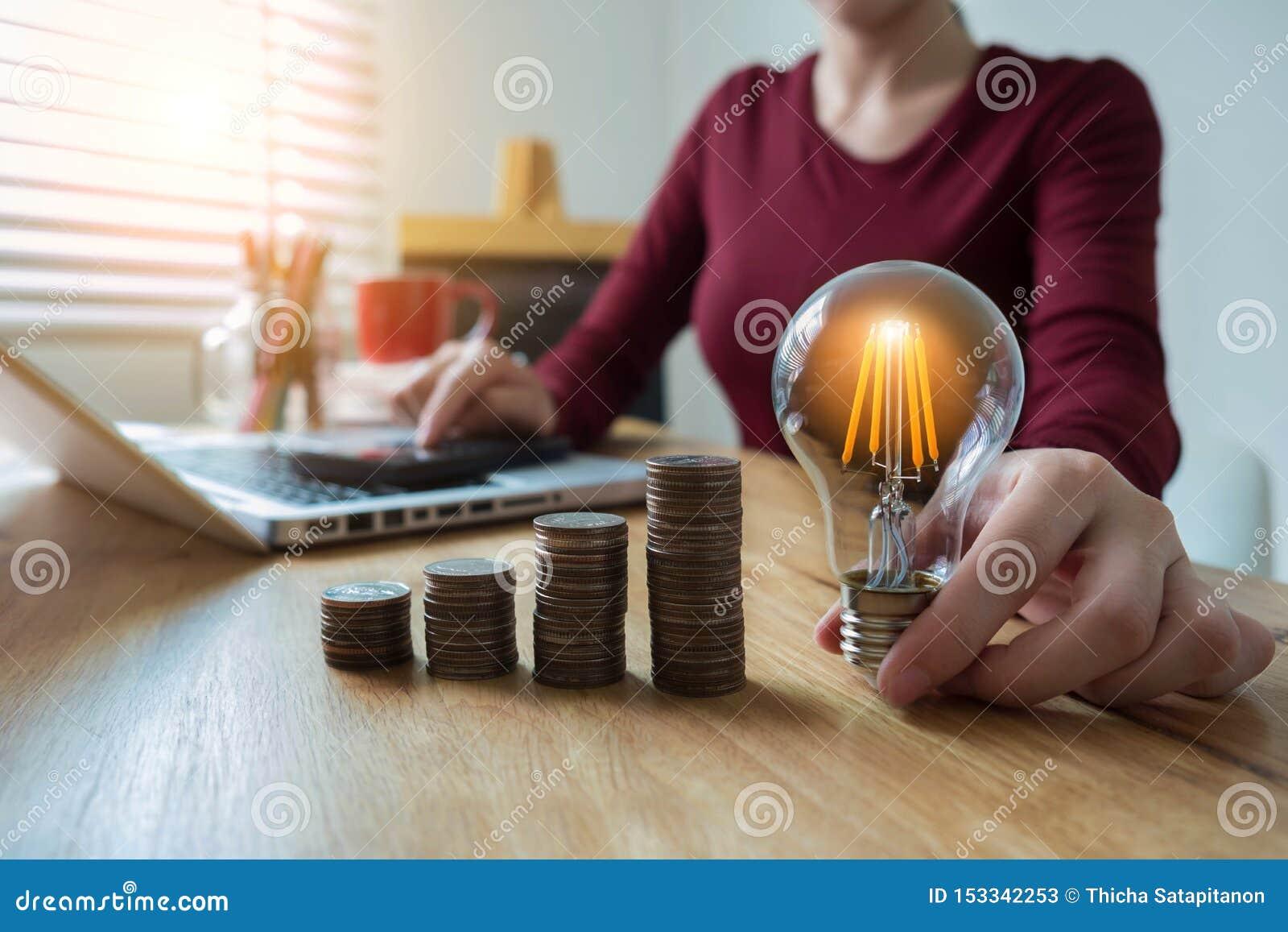 Bombilla de la tenencia de la mano de la mujer de negocios con la pila de las monedas en el escritorio