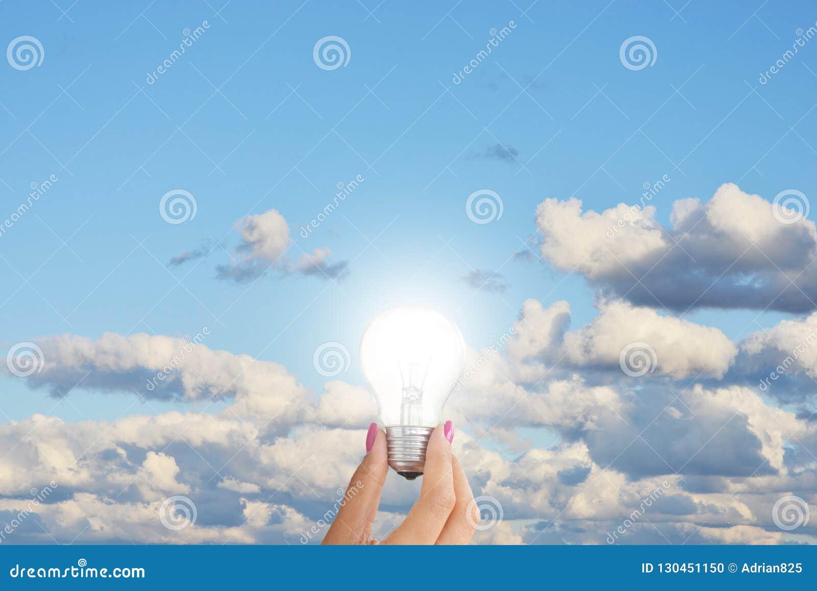 Bombilla en mano de la mujer contra el cielo azul que sugiere concepto de la creatividad