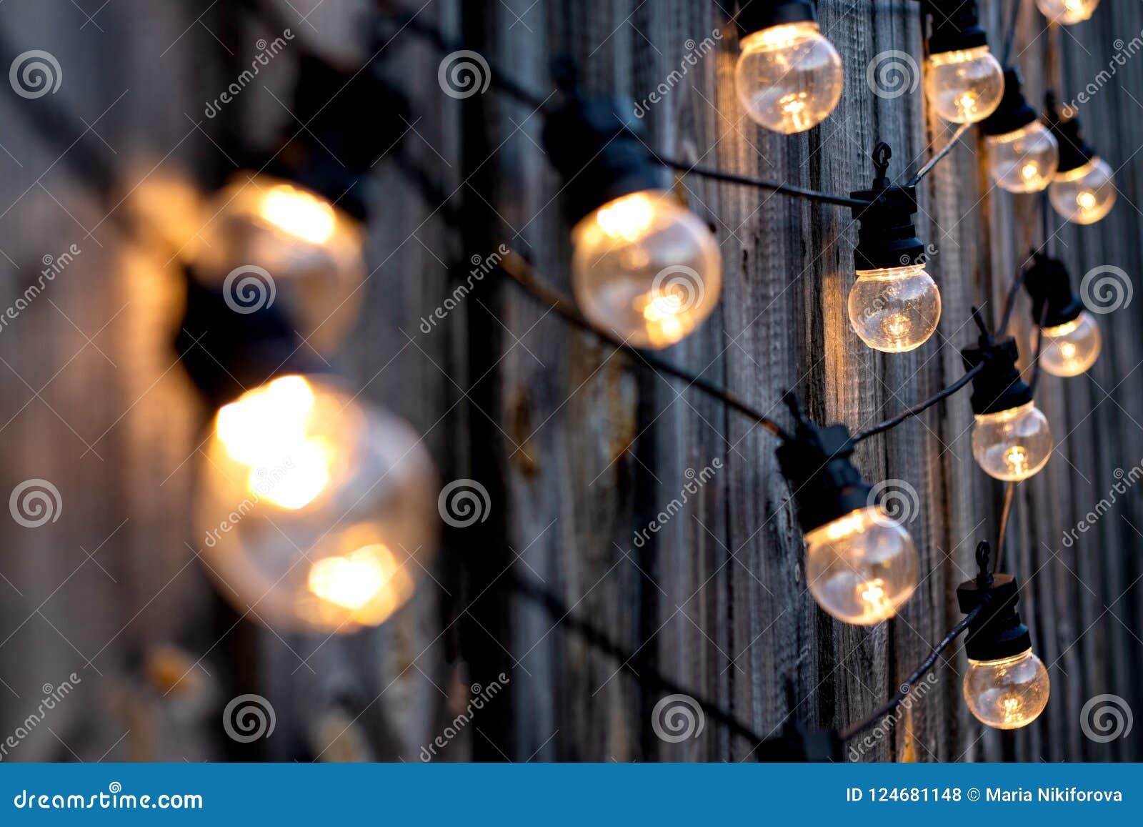 Bombillas calientes del color LED en el viejo fondo de madera en el jardín, copyspace, concepto al aire libre del deciration de l