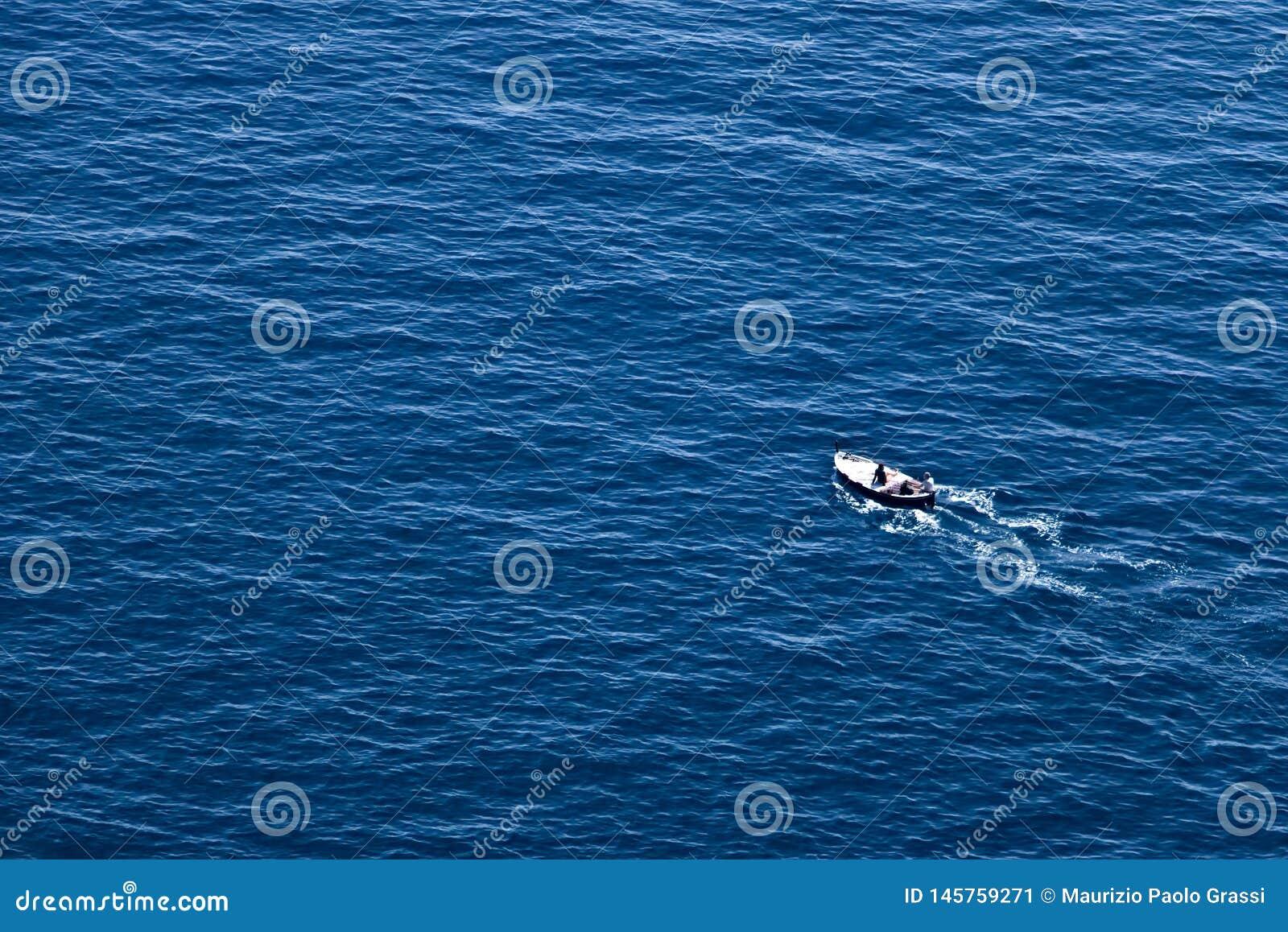 Bonassola, cerca de Cinque Terre, Liguria E Un barco de pesca en el mar azul cerca de las cinco tierras