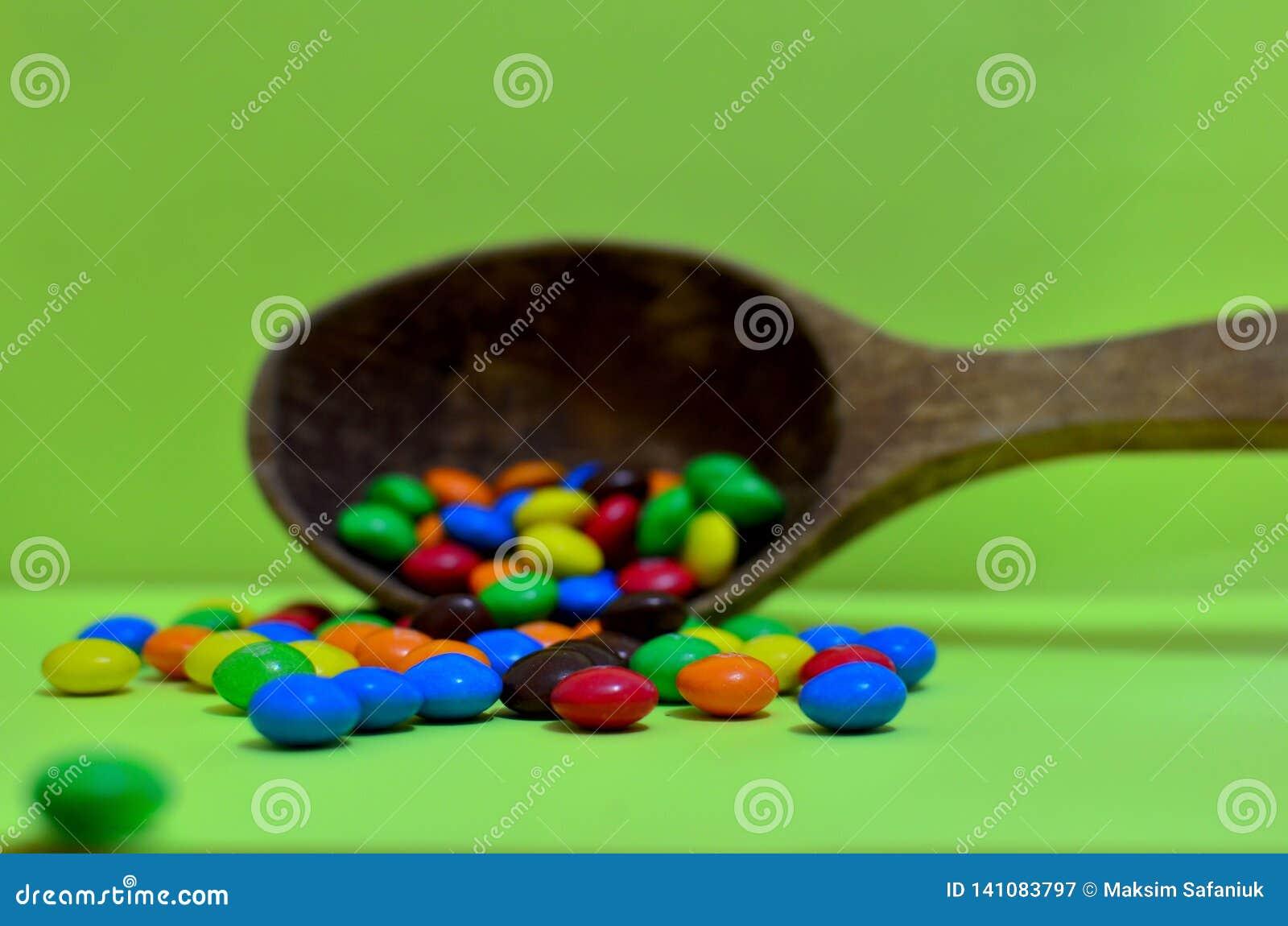 Bonbon sortierte mehrfarbige Schokoladen, Gummibälle in einem hölzernen Löffel auf einem grünen Photon oder Tabletten und Vitamin