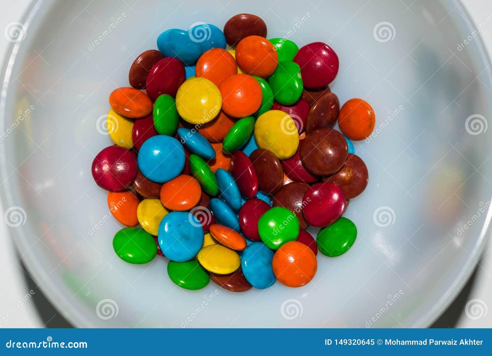 Bonbons au chocolat enduits color?s dans une cuvette blanche