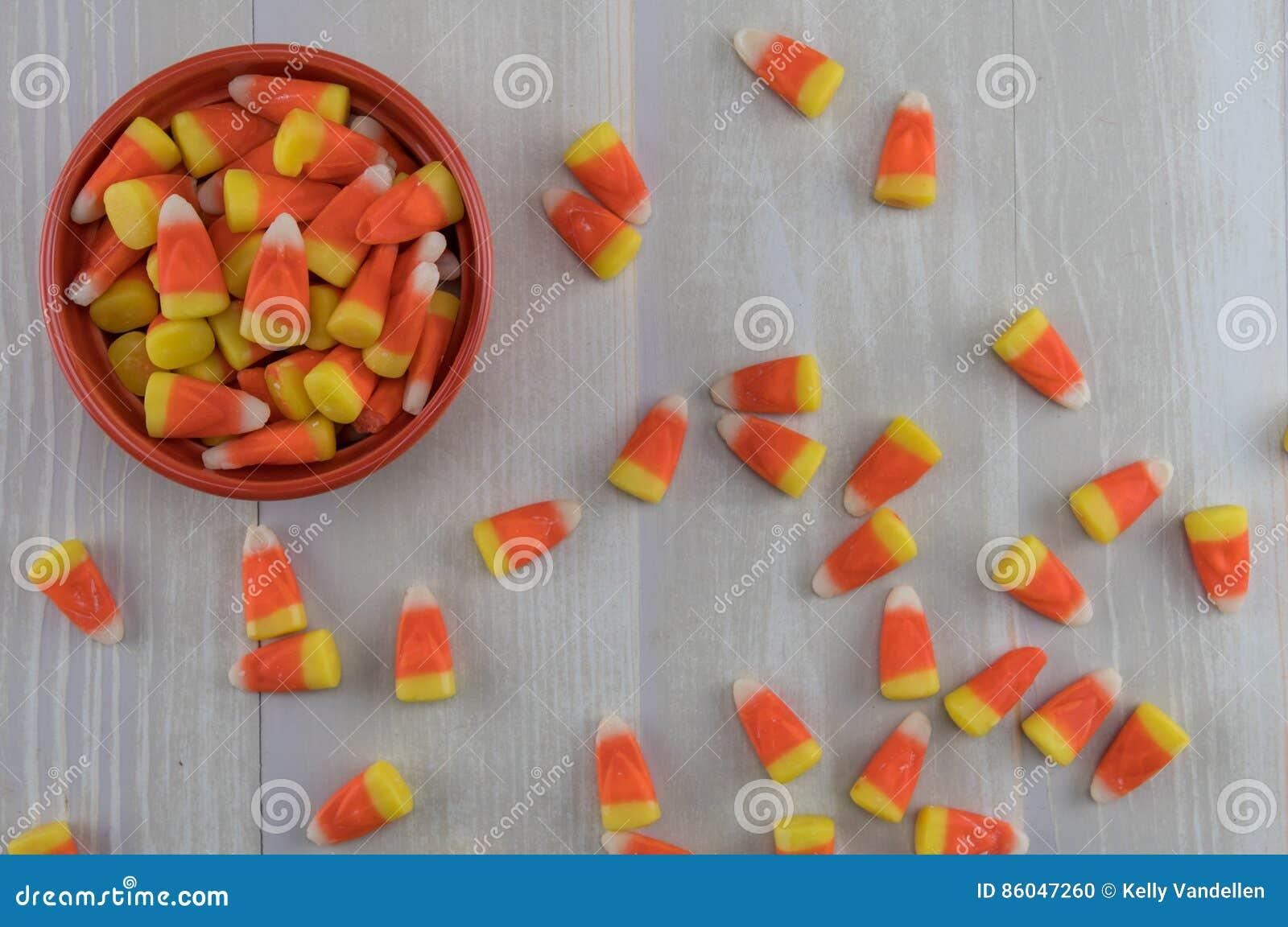 Bonbons au maïs dans la cuvette orange avec la flaque de désordre plus de