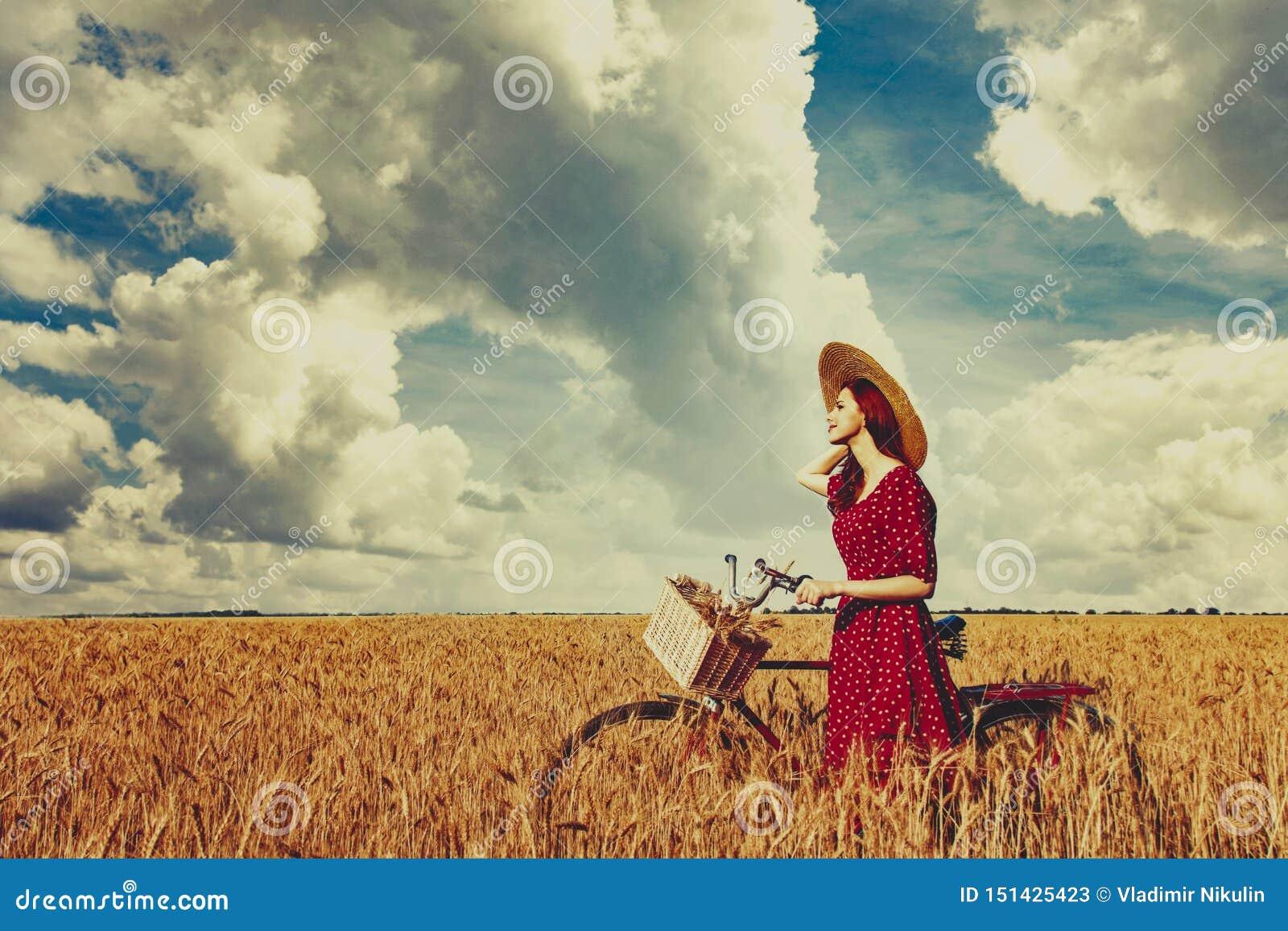 Bondaktig flicka med cykeln på vetefält