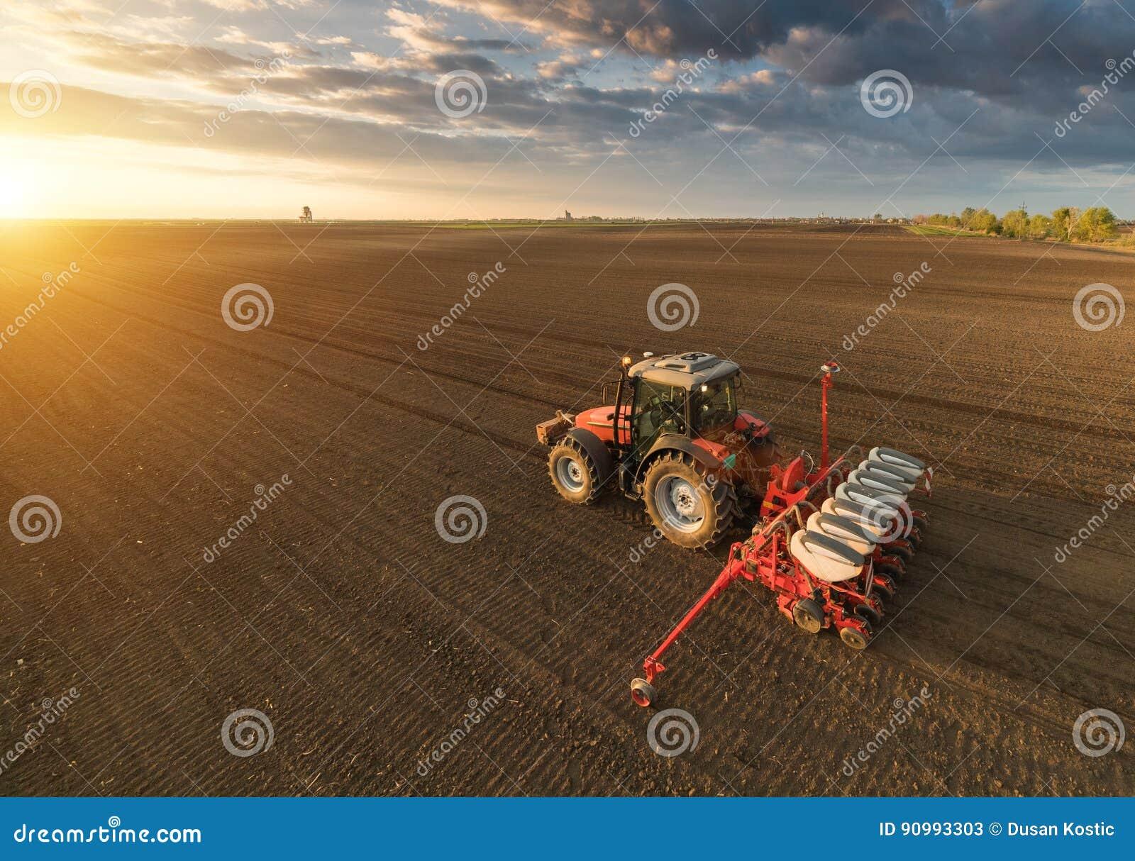 Bonde med att kärna ur för traktor - sådd kantjusterar på det jordbruks- fältet