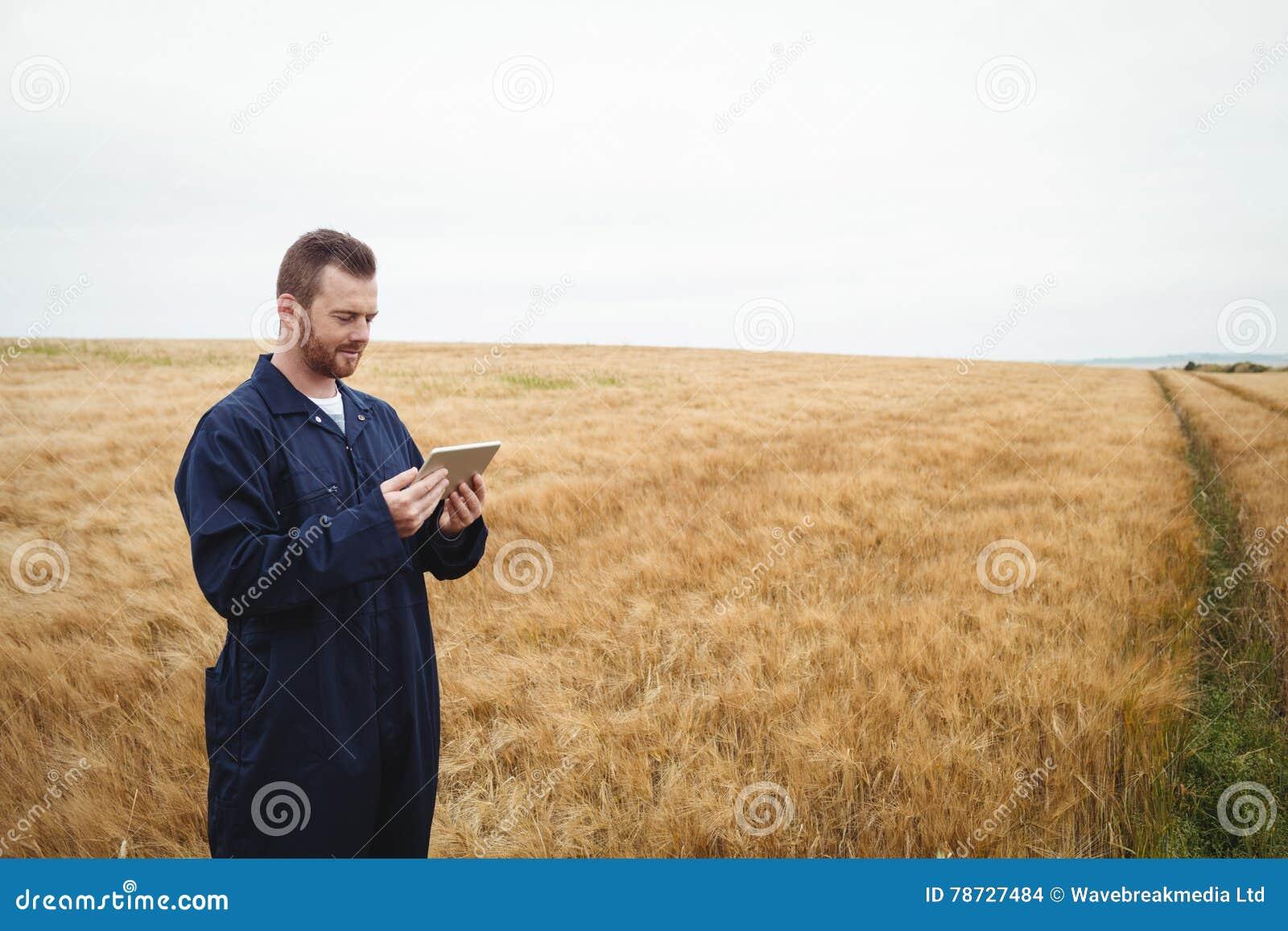 Bonde som använder den digitala minnestavlan i fältet
