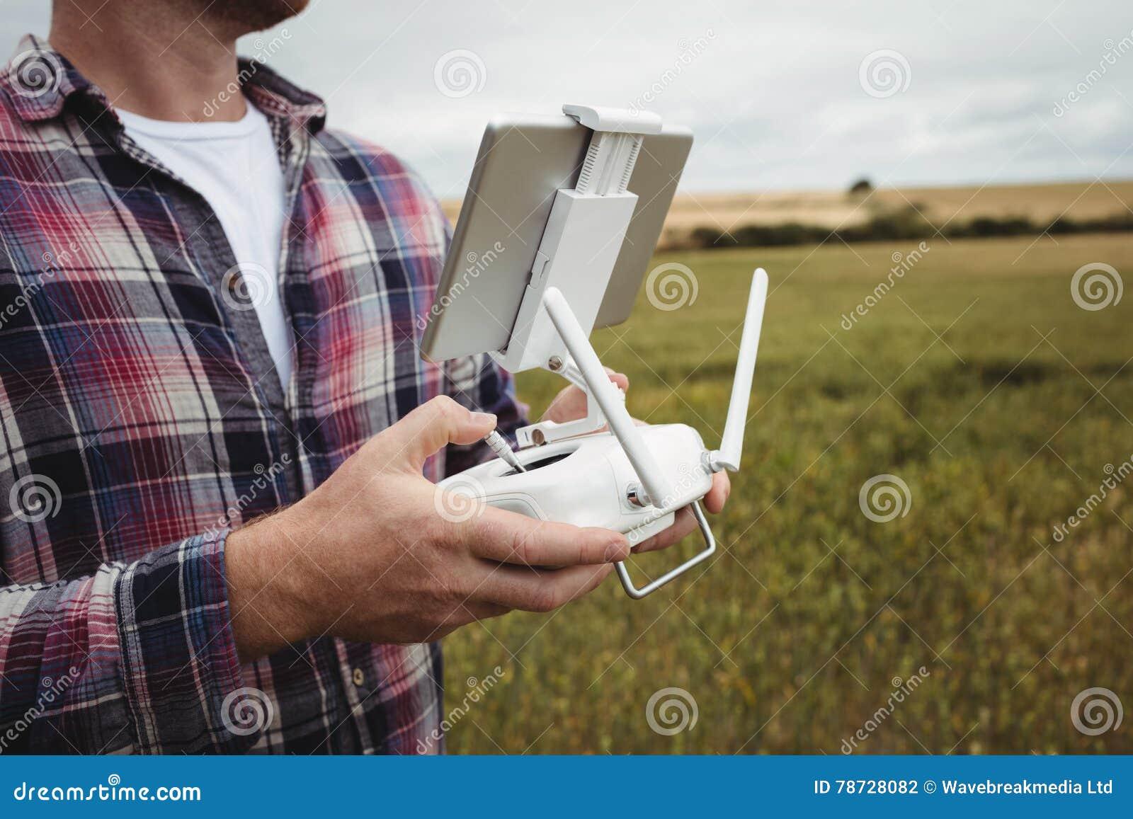 Bonde som använder den jordbruks- apparaten, medan undersöka i fält