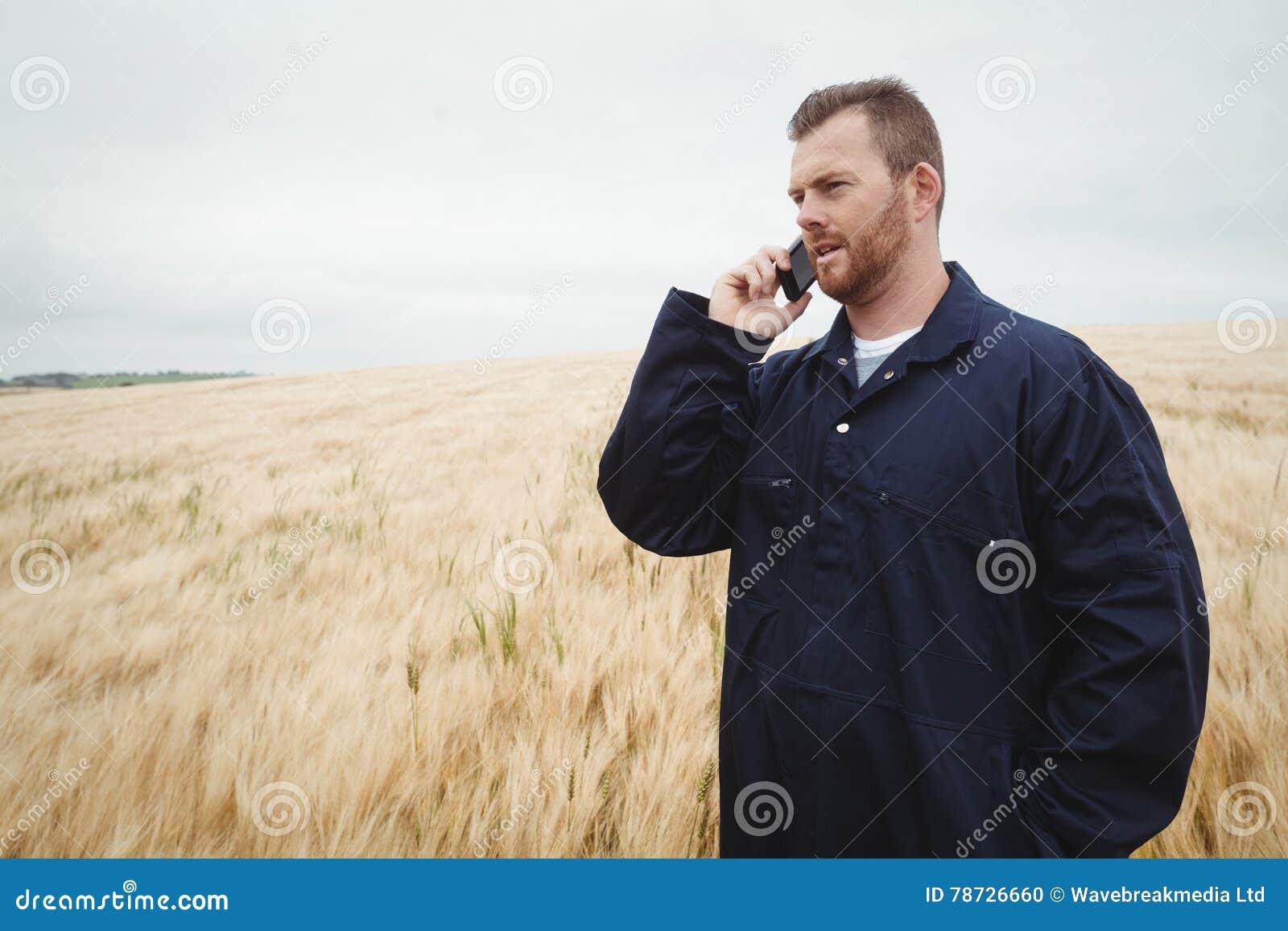 Bonde som talar på mobiltelefonen i fältet
