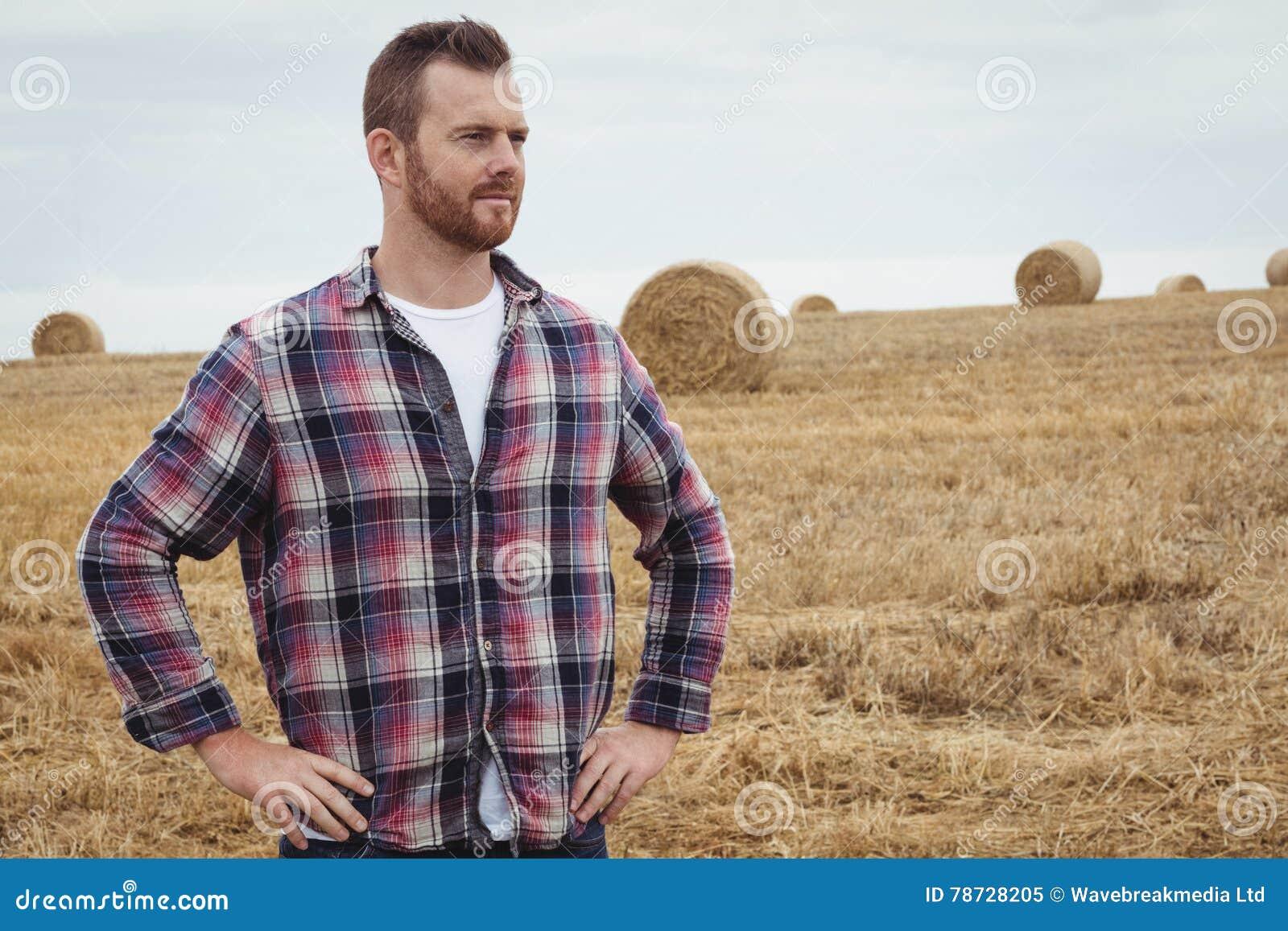 Bondeanseende med händer på höfter i fältet