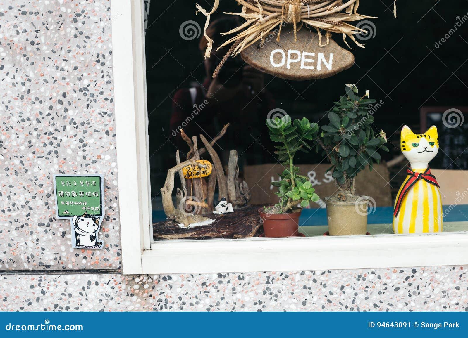 A boneca bonito do gato e abre o sinal de madeira largo através do vidro da janela de loja