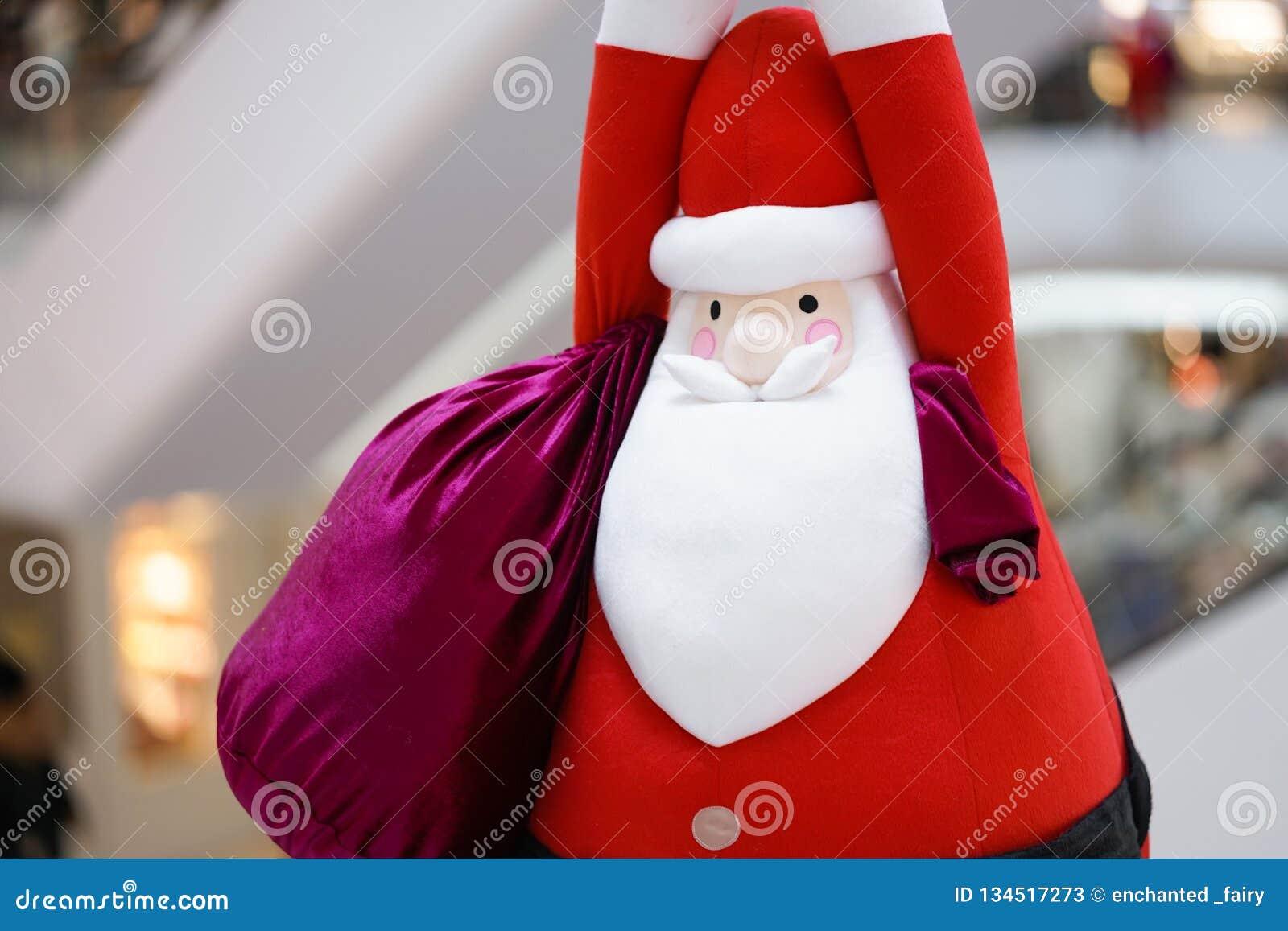 Boneca de Santa Claus Uma boneca macia do luxuoso de Santa Claus do gigante está pendurando para baixo do teto com um saco grande