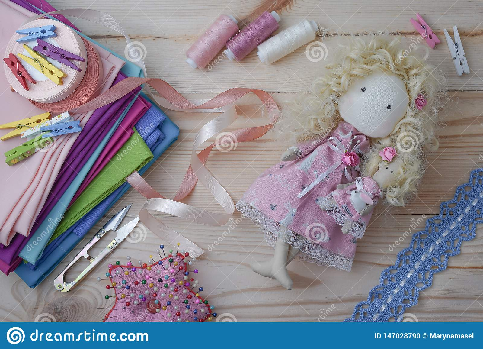 Boneca feito a mão bonito em uma tabela de madeira com telas coloridas, laço feito malha, fitas pasteis e mobília costurar