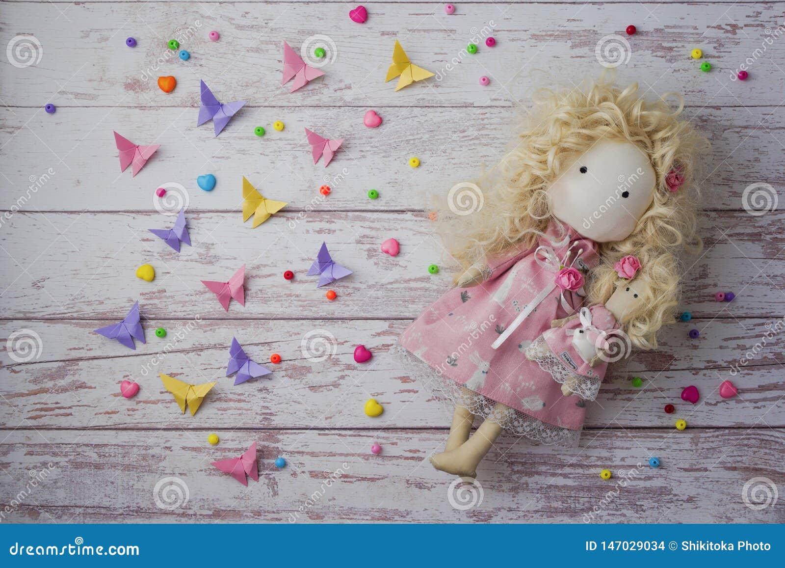 Boneca feito a mão da tela perto dos grânulos coloridos, borboletas de papel