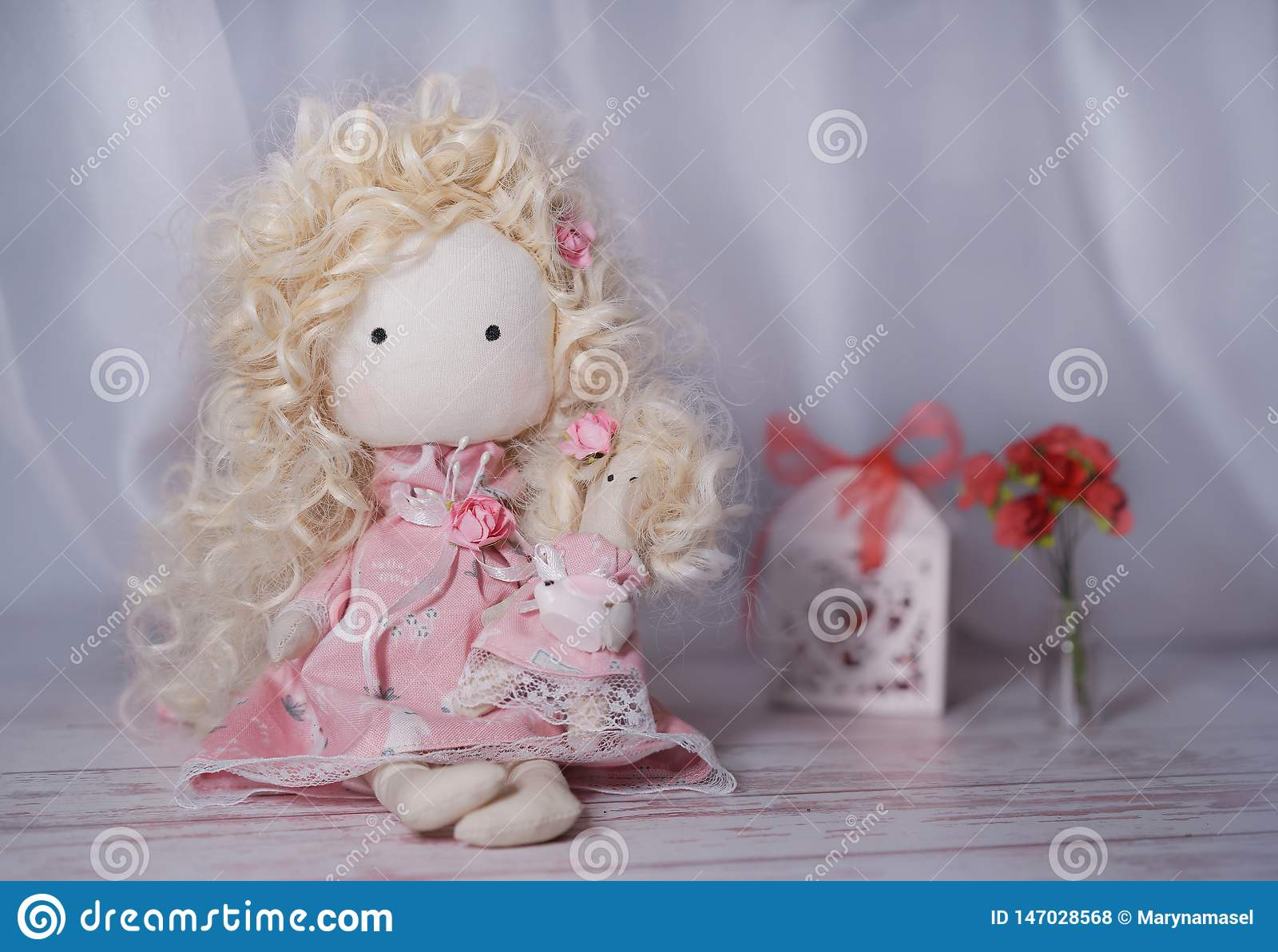 Boneca feito a mão em uma tabela de madeira branca com flores de papel e caixa de presente