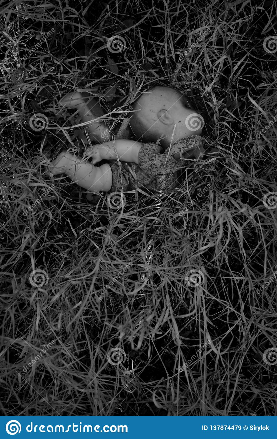 Boneca plástica queimada nas madeiras
