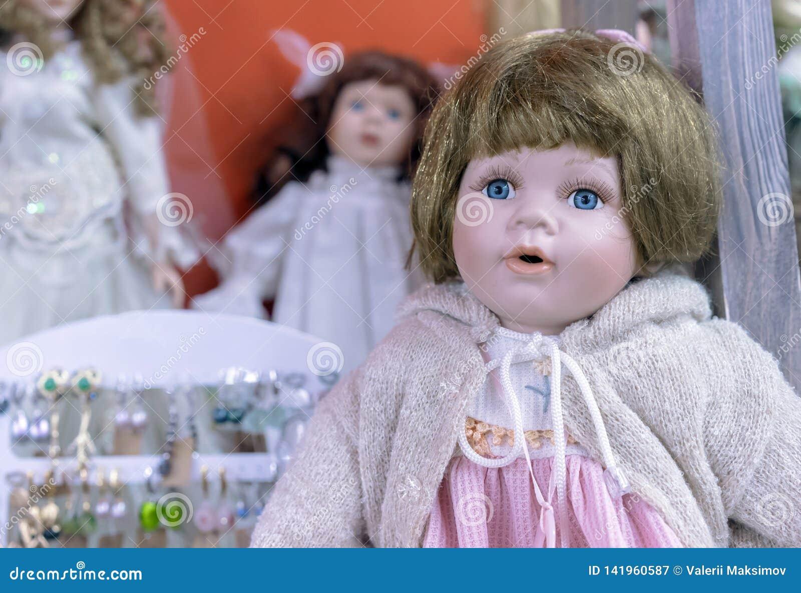 Boneca realística com olhos azuis em uma camiseta bege e em um vestido cor-de-rosa