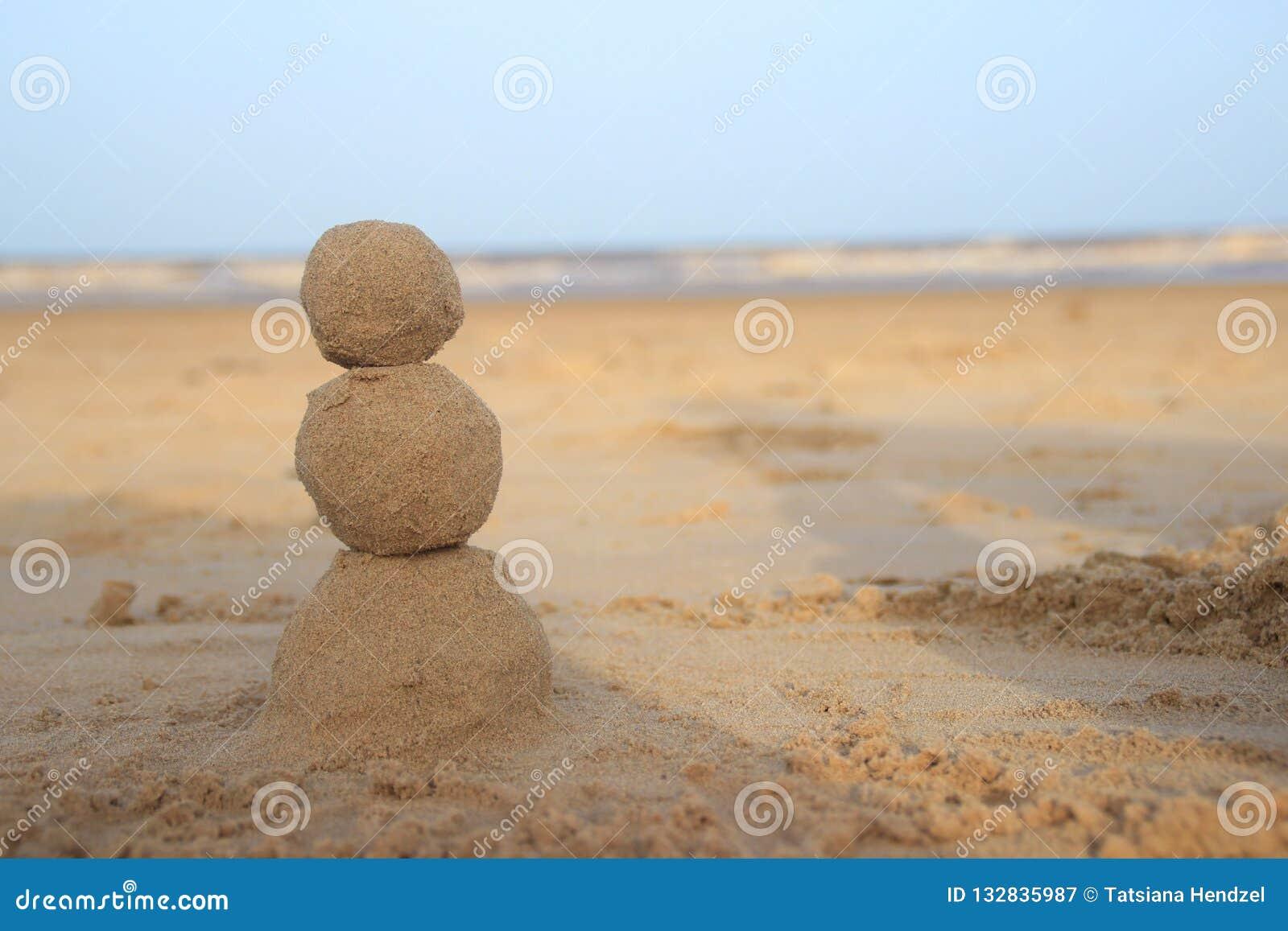 Boneco de neve da areia para aquelas que comemoram o ano novo pelo mar