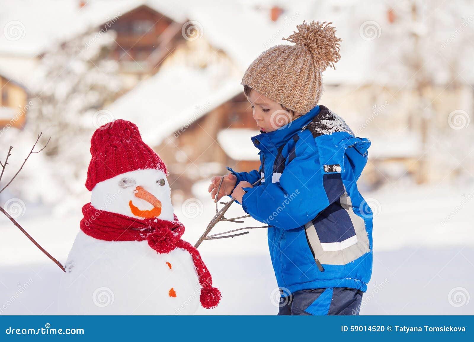 Boneco de neve feliz da construção da criança bonita no jardim, inverno