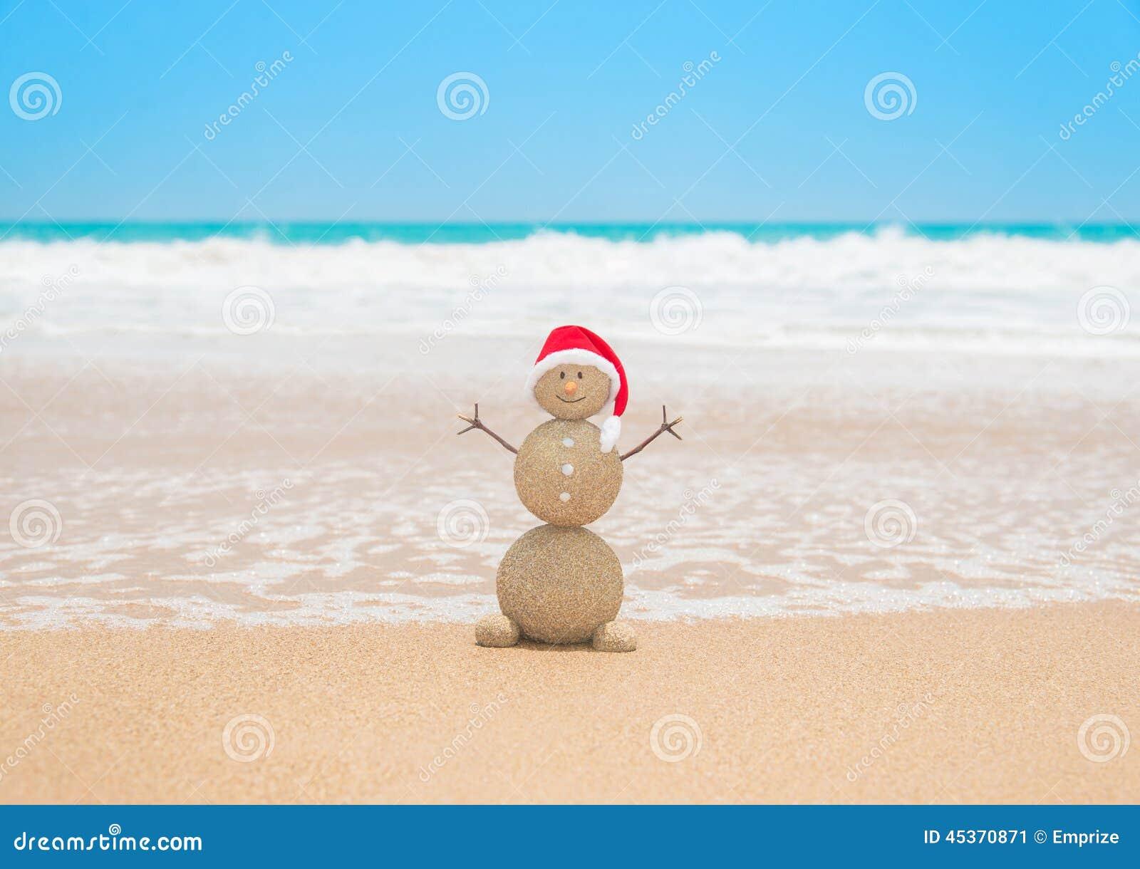 Bonhomme de neige arénacé de Noël dans le chapeau de Santa à la plage tropicale