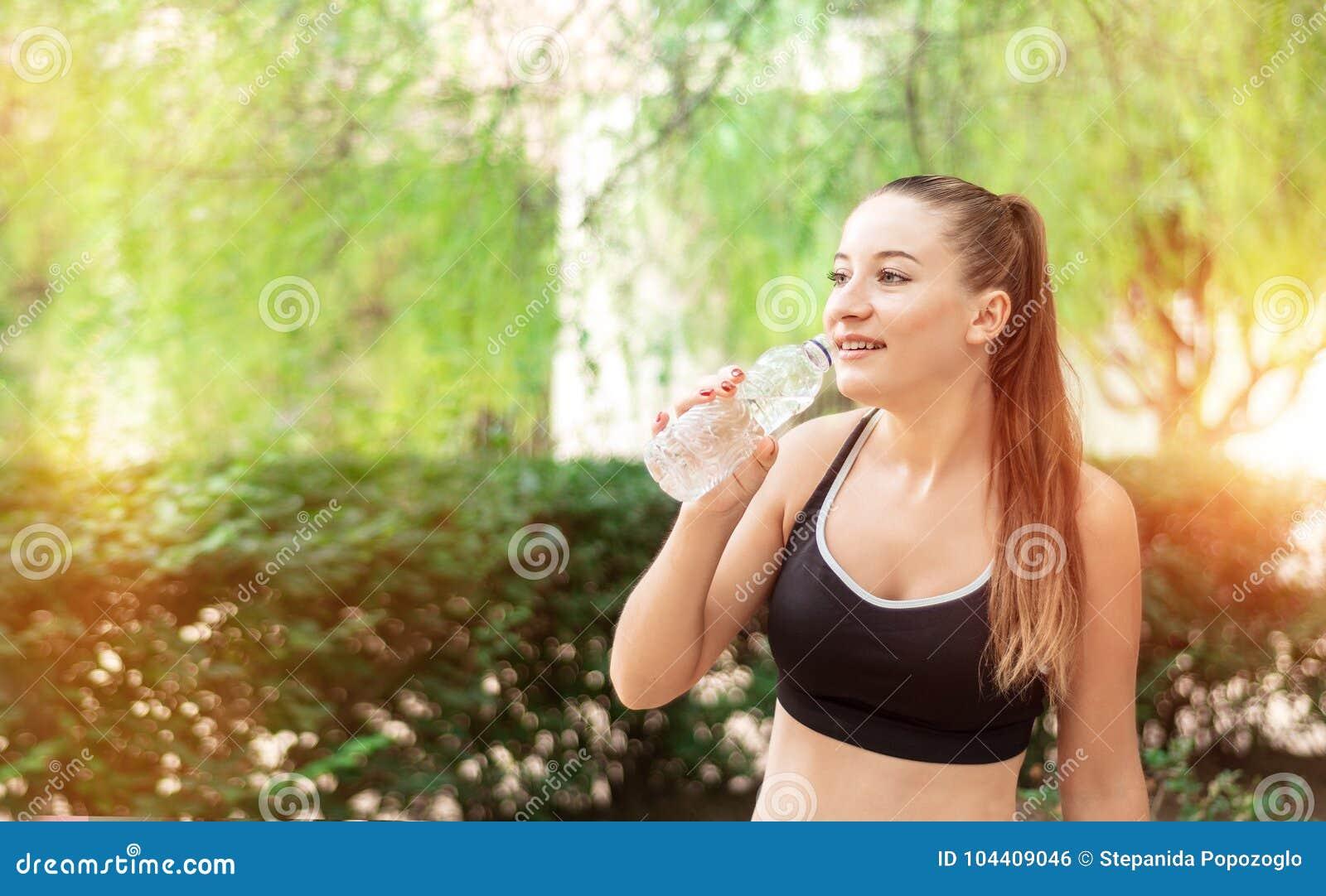 Bonita, a menina do esporte da aptidão com rabo de cavalo bebe a água no