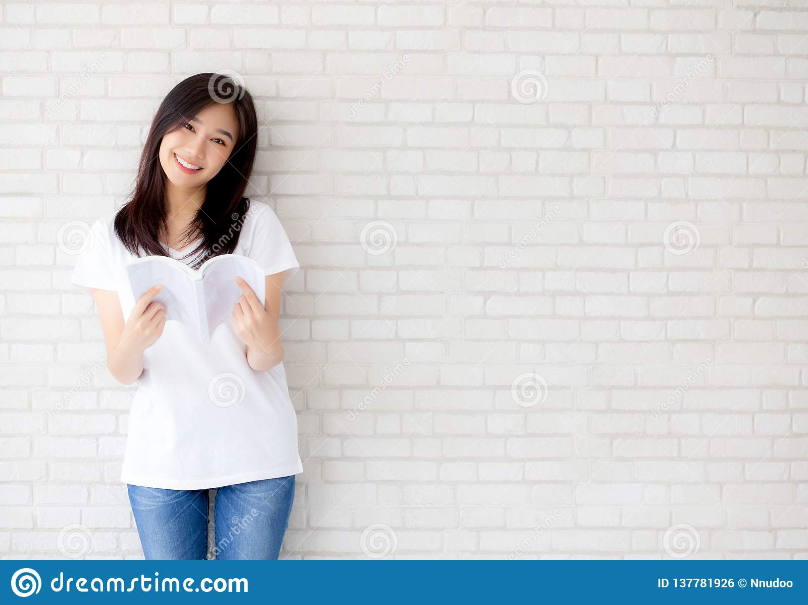 Bonito da felicidade asiática nova da mulher do retrato relaxe o livro de leitura ereto no fundo concreto do branco do cimento