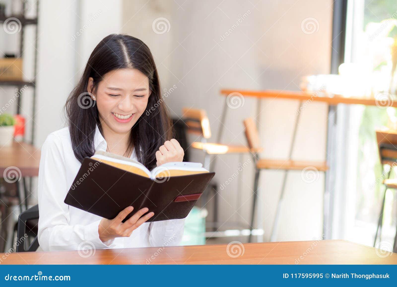 Bonito da leitura asiática da jovem mulher do negócio do retrato no caderno com sucesso na tabela