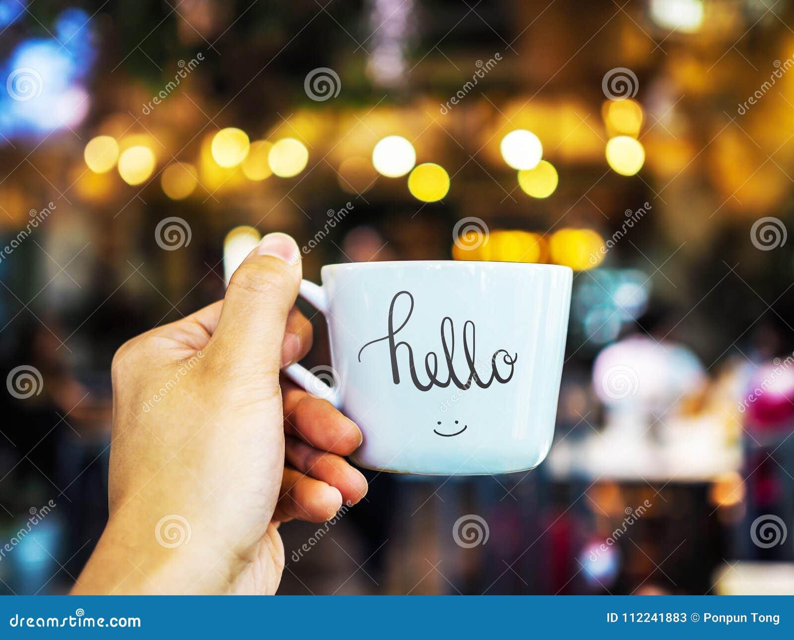 Bonjour écriture de main des textes sur la tasse avec la participation de main