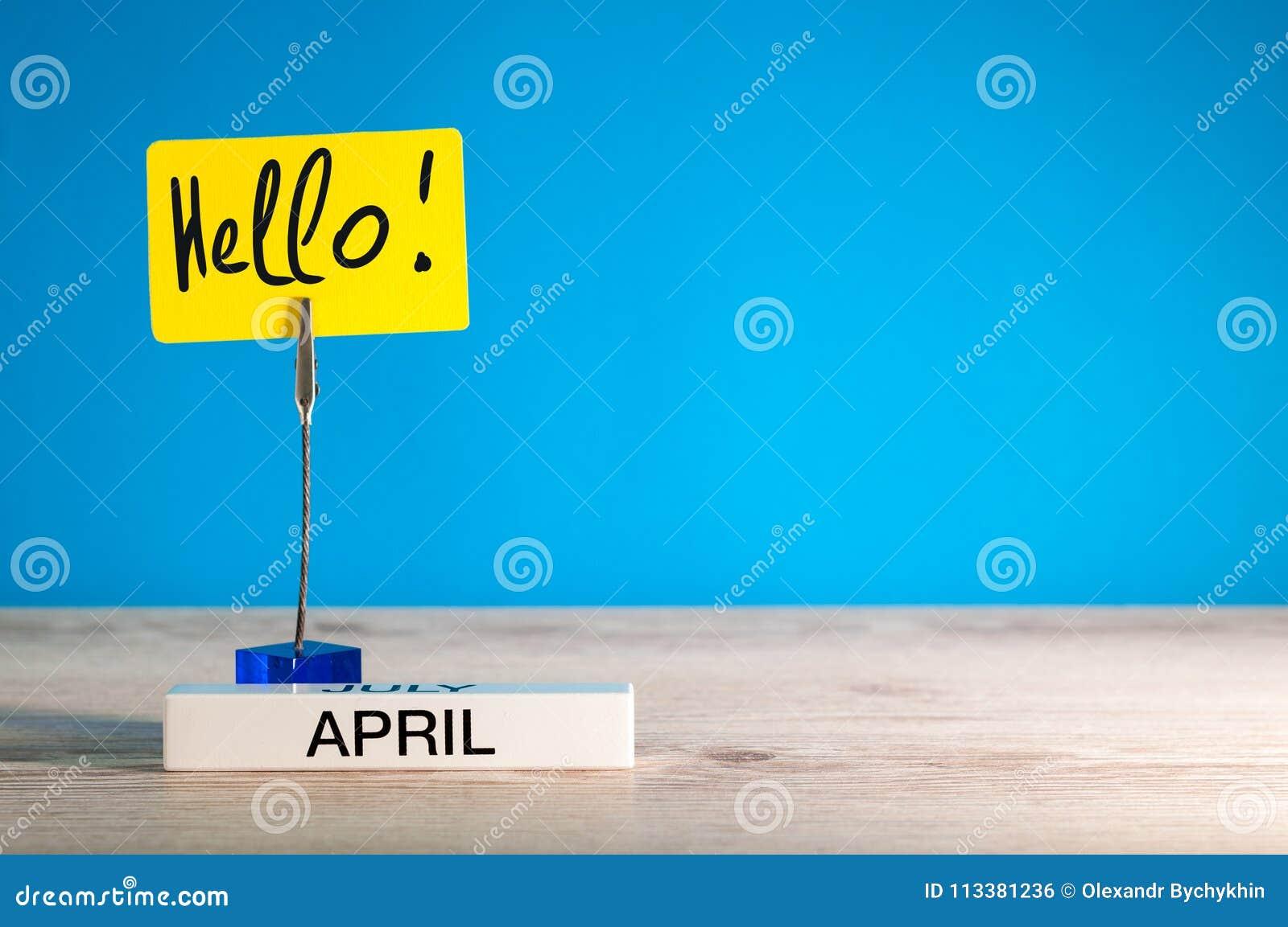 Bonjour avril - un rappel d inscription de l arrivée du ` s de mois sur la table, fond bleu, avec l espace vide pour le texte
