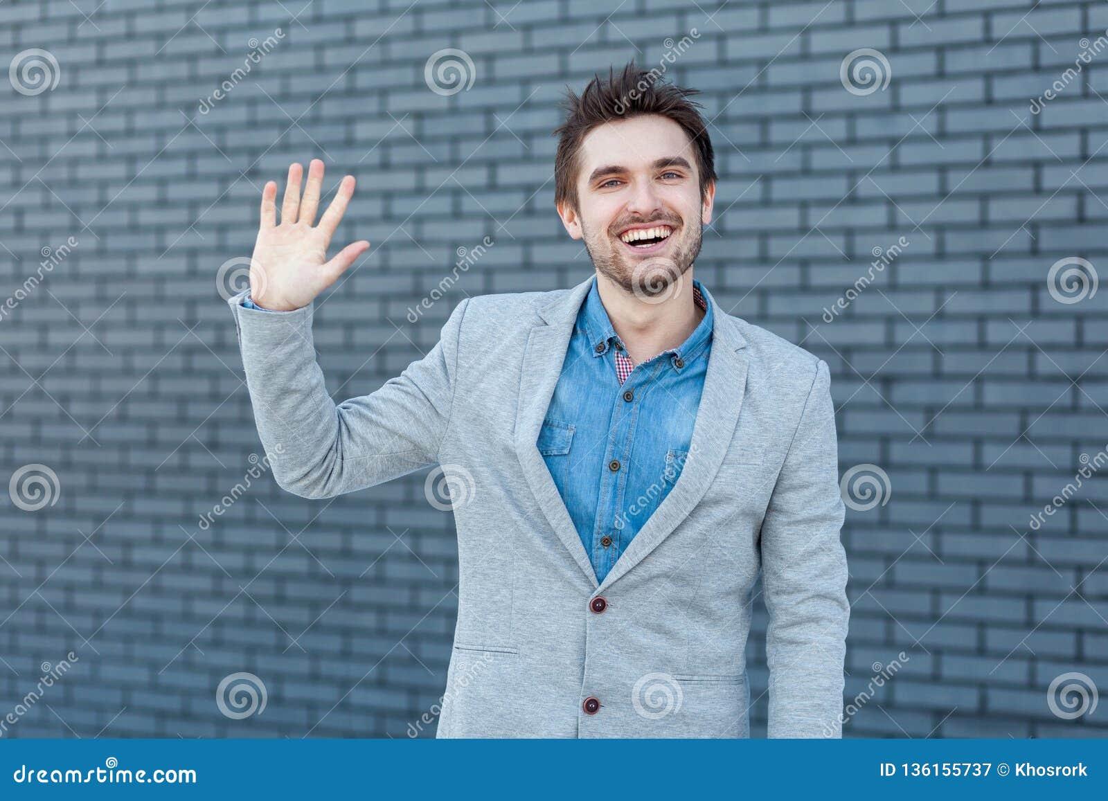 Bonjour, gentil de vous voir Portrait d homme barbu bel heureux dans le style occasionnel tenant et regardant la caméra avec le g