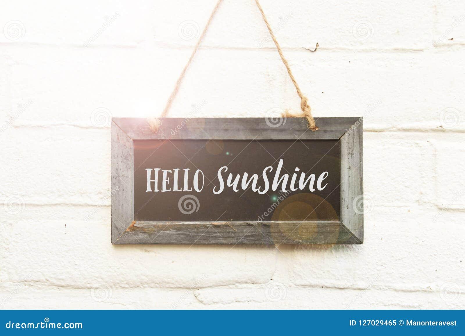 Bonjour texte bienvenu de soleil sur le tableau accrochant sur la brique blanche