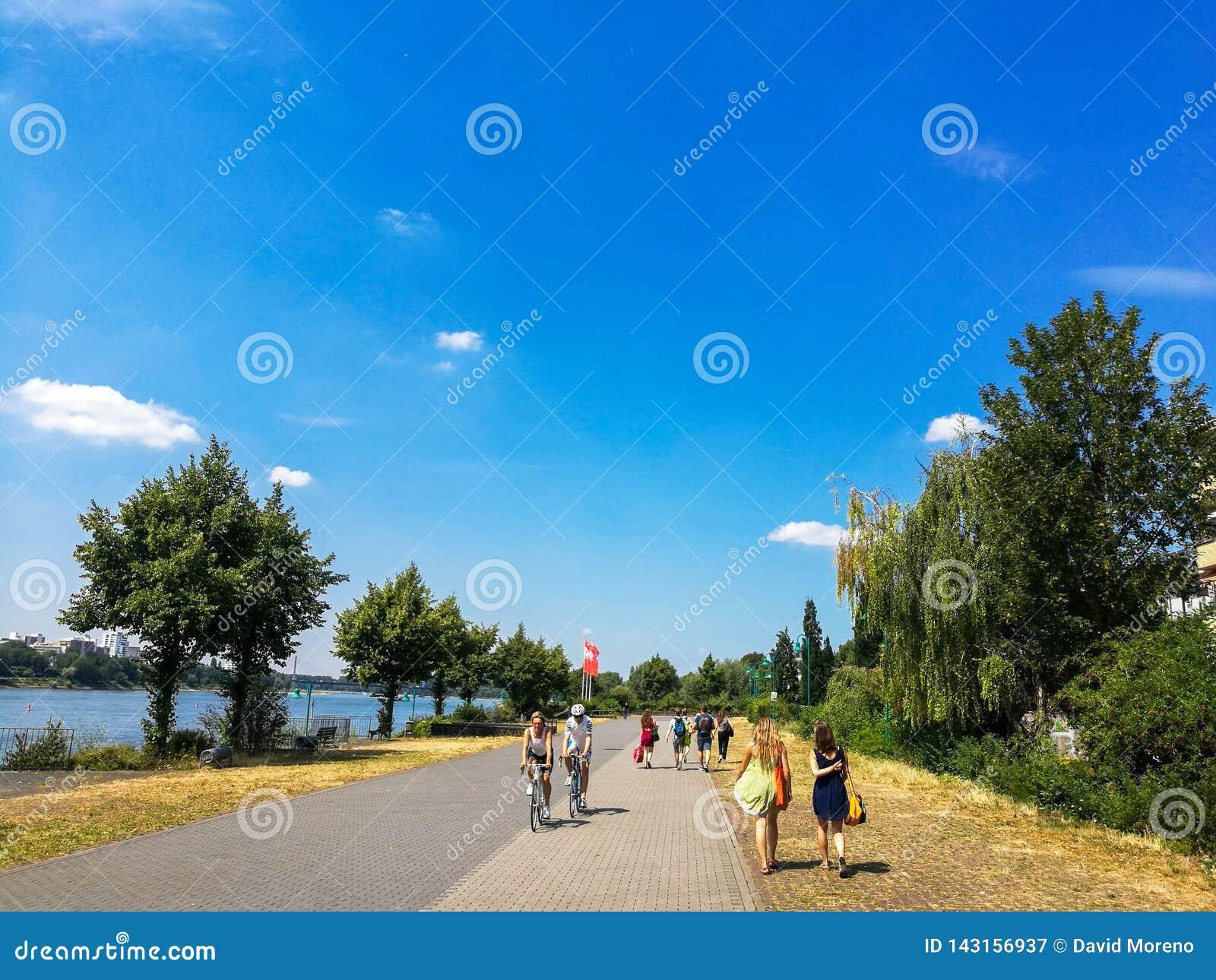 BONN - 13 juli: mensen in het park in Bonn, Duitsland die langs de Rijn-rivier lopen